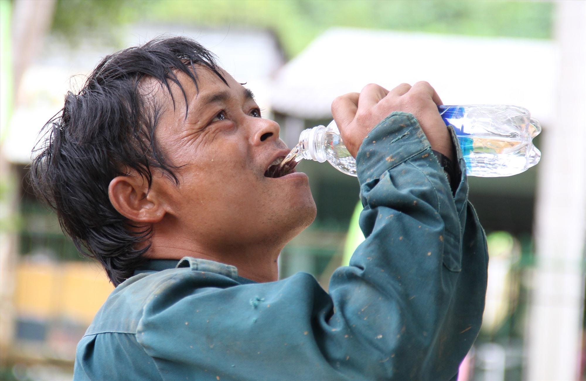Một phụ huynh nghỉ tay uống nước, rồi tiếp tục cùng đội làm nhiệm vụ quét dọn sân trường. Ảnh: A.N