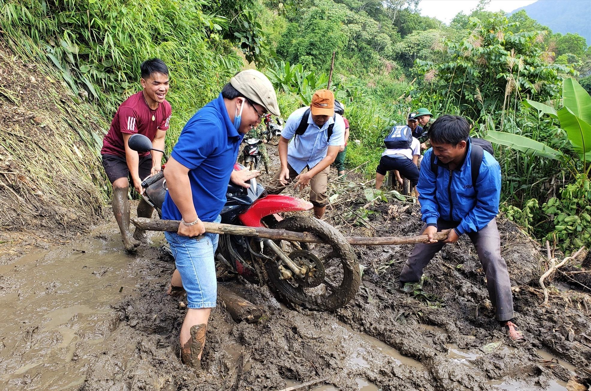 Người dân khiêng xe qua khu vực sạt lở trên tuyến đường từ xã A Xan vào Ga Ri, huyện Tây Giang. Ảnh:THANH THẮNG