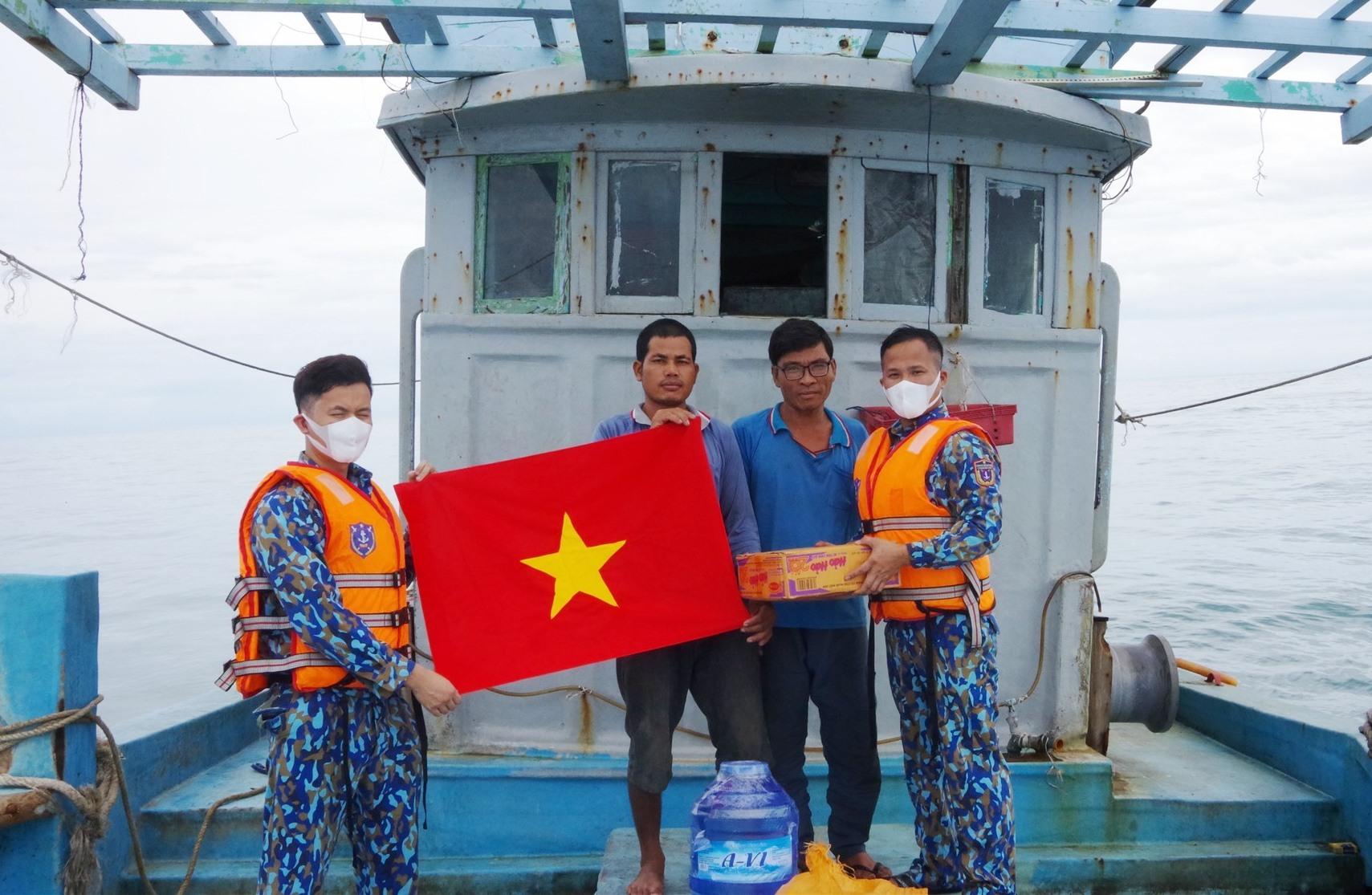 Tặng thực phẩm nước ngọt cho ngư dân trên tàu trước khi lai dắt vào bờ. Ảnh: NAM TRUNG