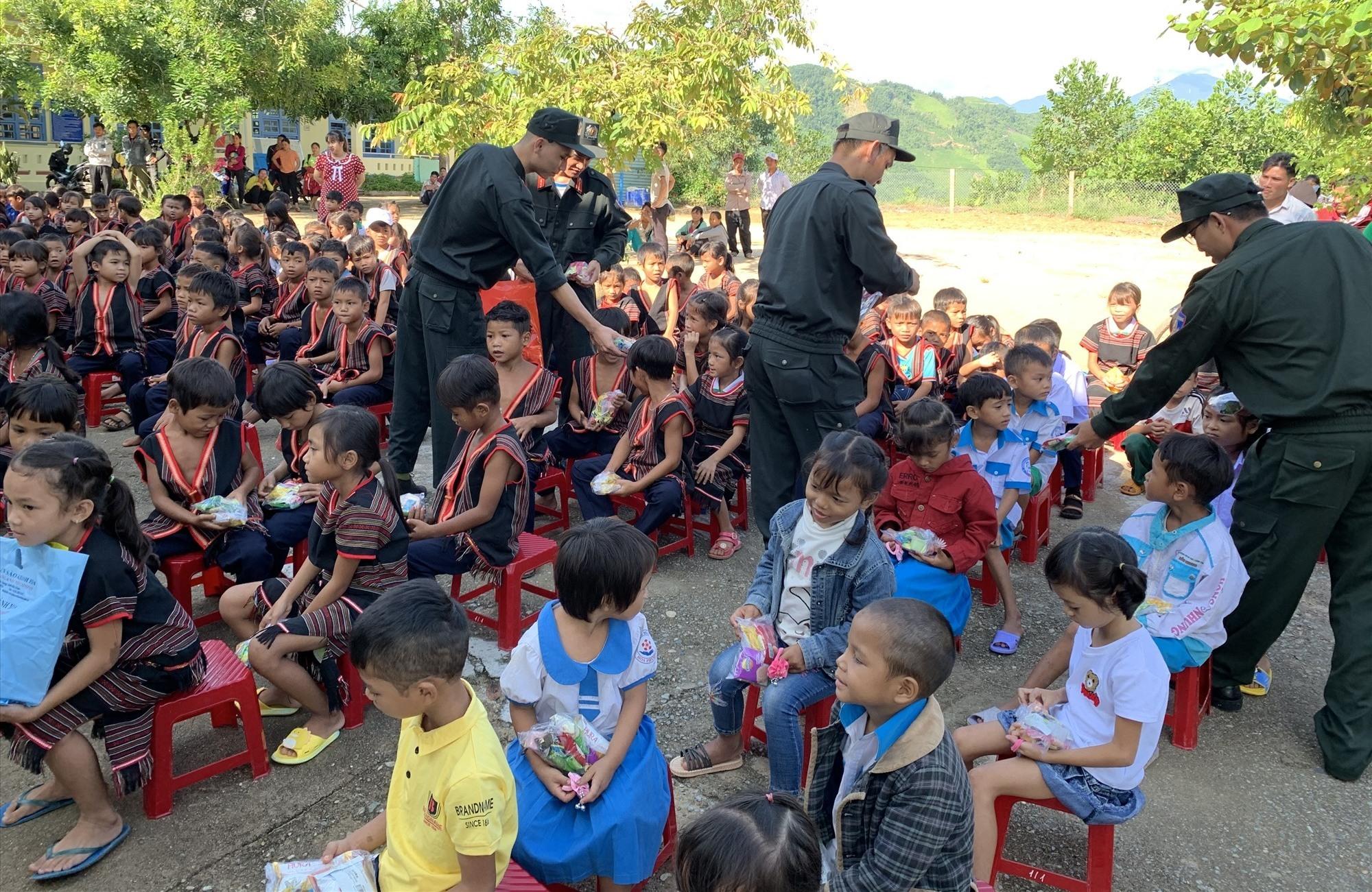 Cán bộ, chiến sĩ của đơn vị giao lưu, tặng quà cho các em nhỏ Trường Tiểu học Nông Văn Dền. Ảnh: Đ.V