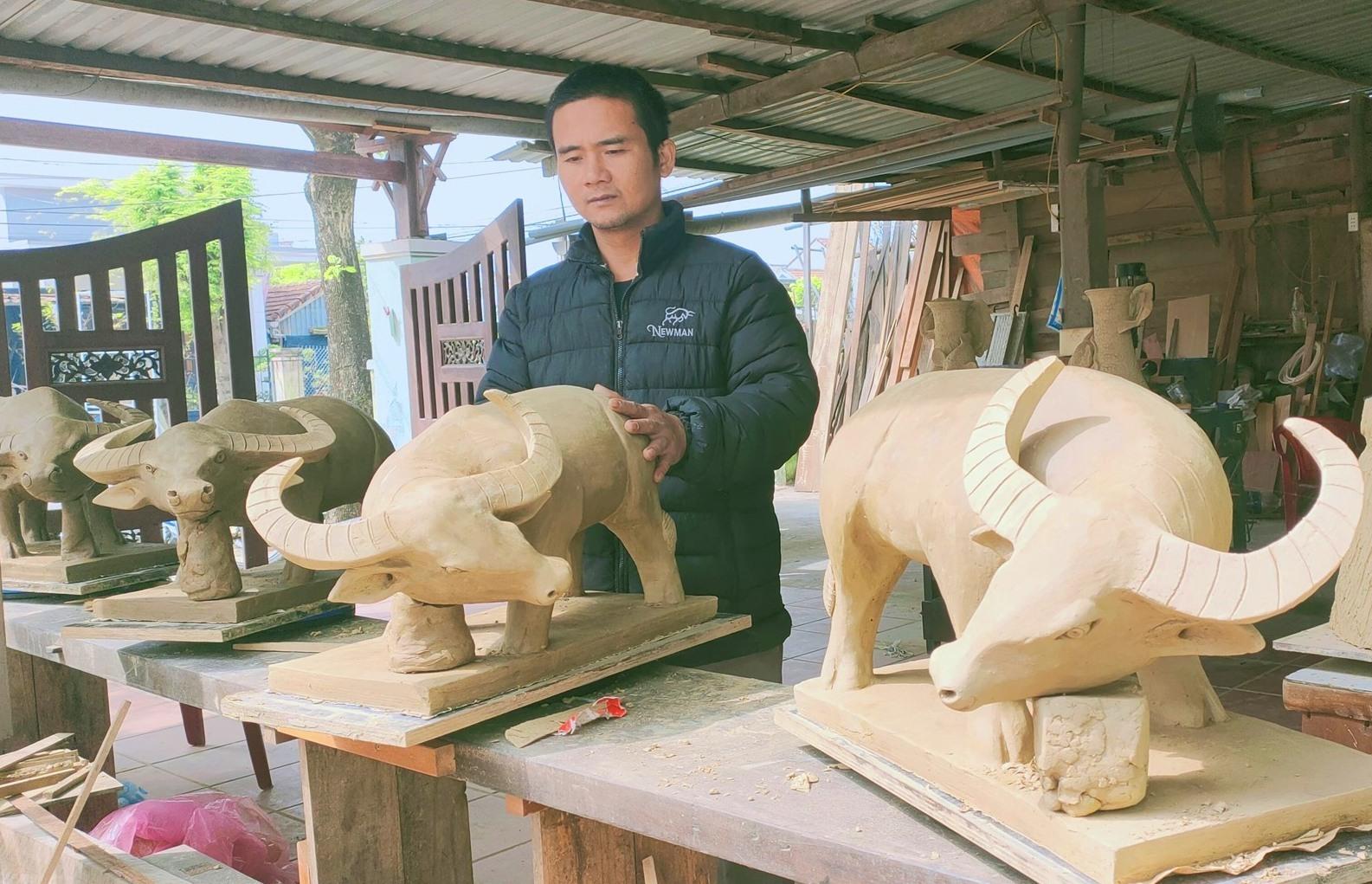 Nguyễn Văn Hoàng bên tượng trâu đất.