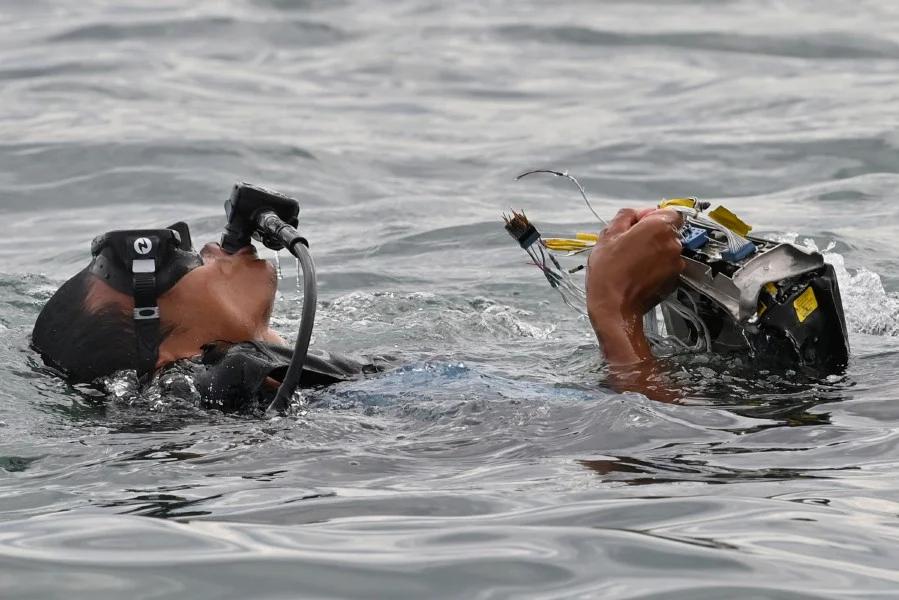 Thợ lặn Indonesia mang lên mặt nước một mảnh vỡ của máy bay gần đảo Lancang. Ảnh: AFP.