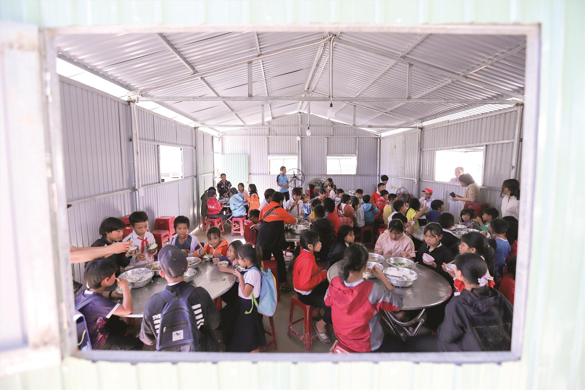 Bữa cơm của học sinh Trường Phổ thông dân tộc bán trú tiểu học và THCS Phước Kim trong căn nhà mái tôn vừa được dựng tạm, vì nhà ăn tập thể đã bị con suối phía sau trường phá sập một góc, nứt toác tường và nền.