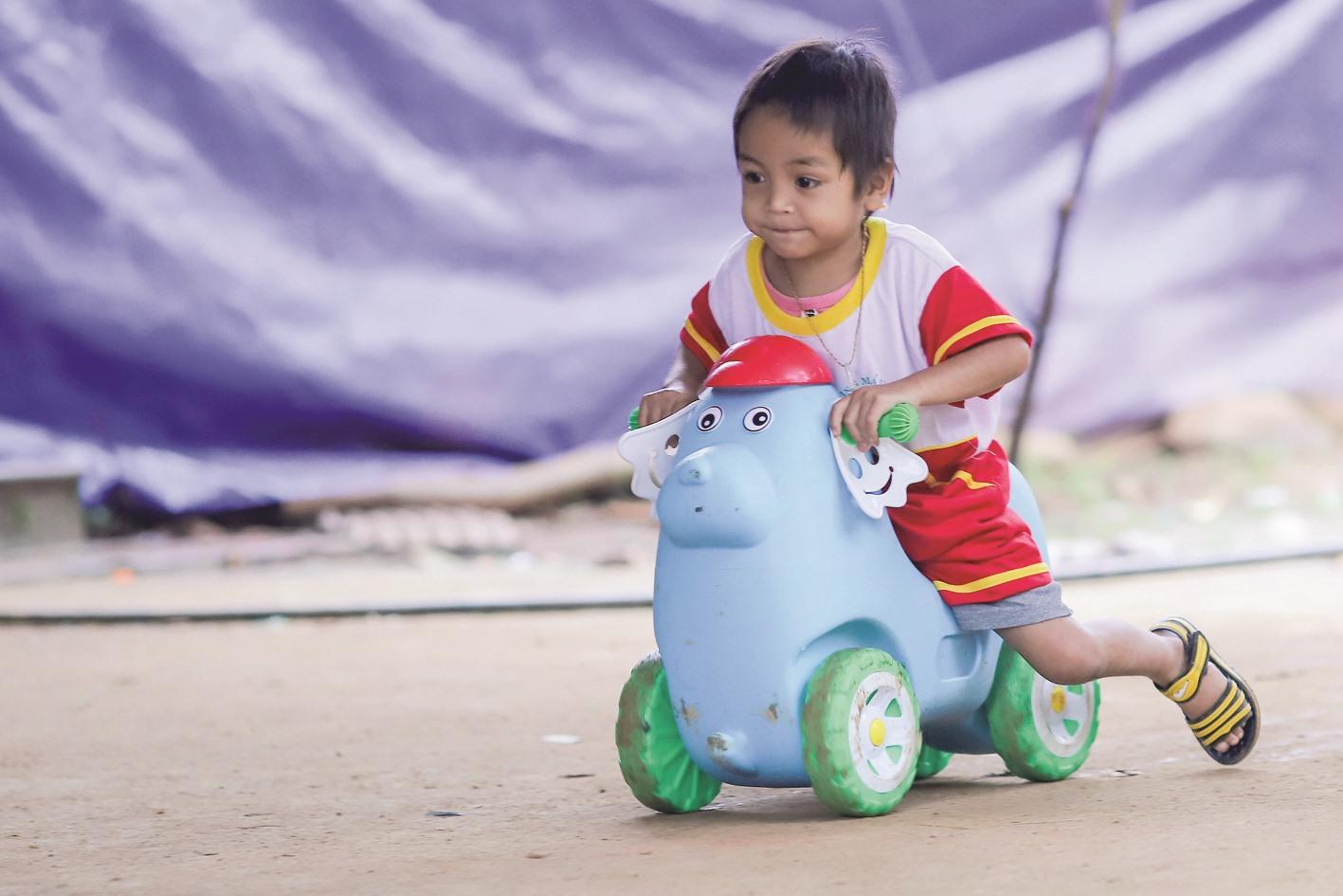 Em Hồ Quang Minh Hoài, 4 tuổi, chơi trong khu vực sân trường mầm non ở nóc ông Đề. Trong thảm họa sạt lở núi, mẹ và em của Hoài đều gặp bất hạnh.