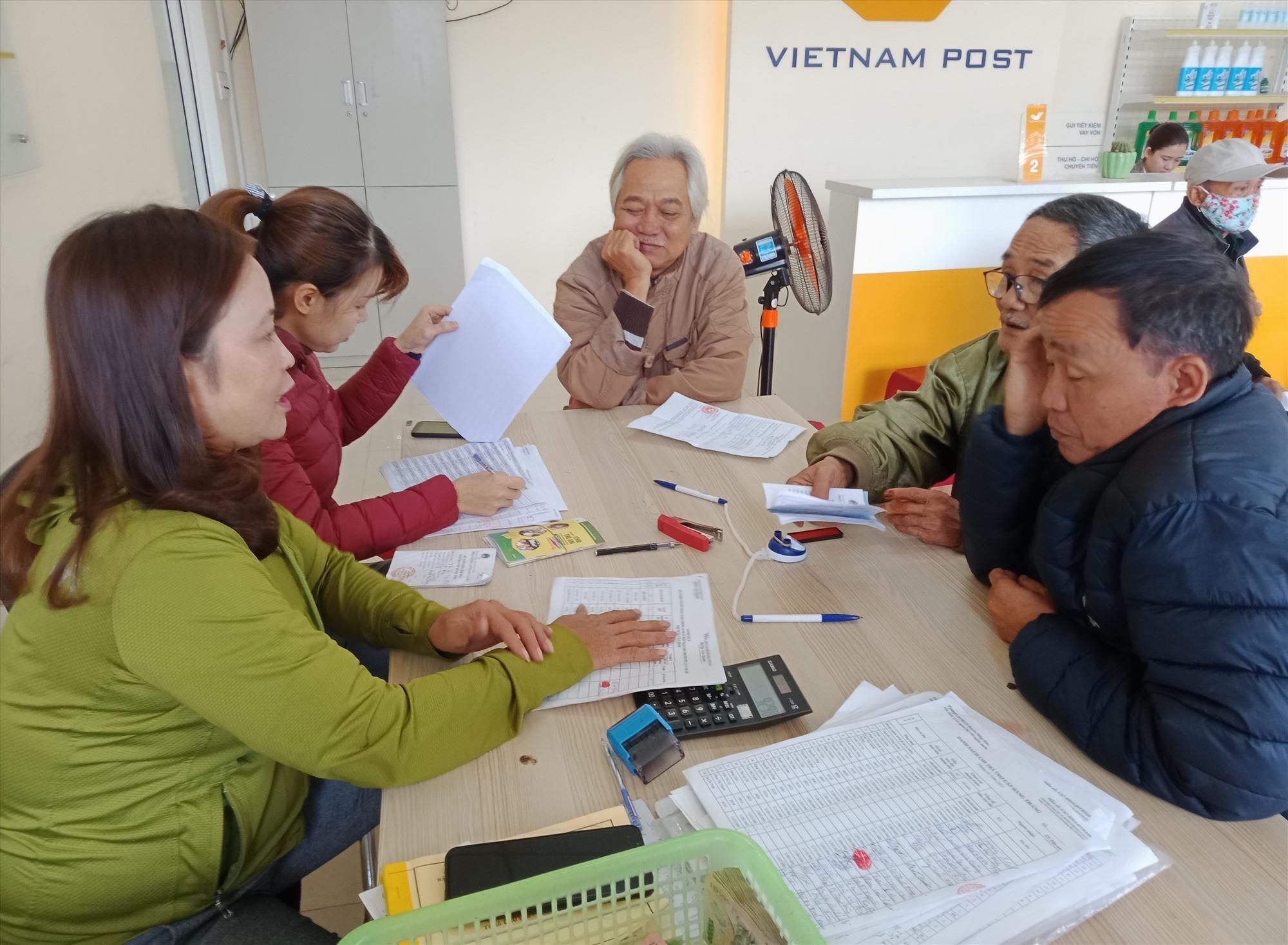 Nhân viên Bưu điện Hiệp Đức chi trả kịp thời tiền trợ cấp cho người dân để có điều kiện mua sắm tết. Ảnh: V.M