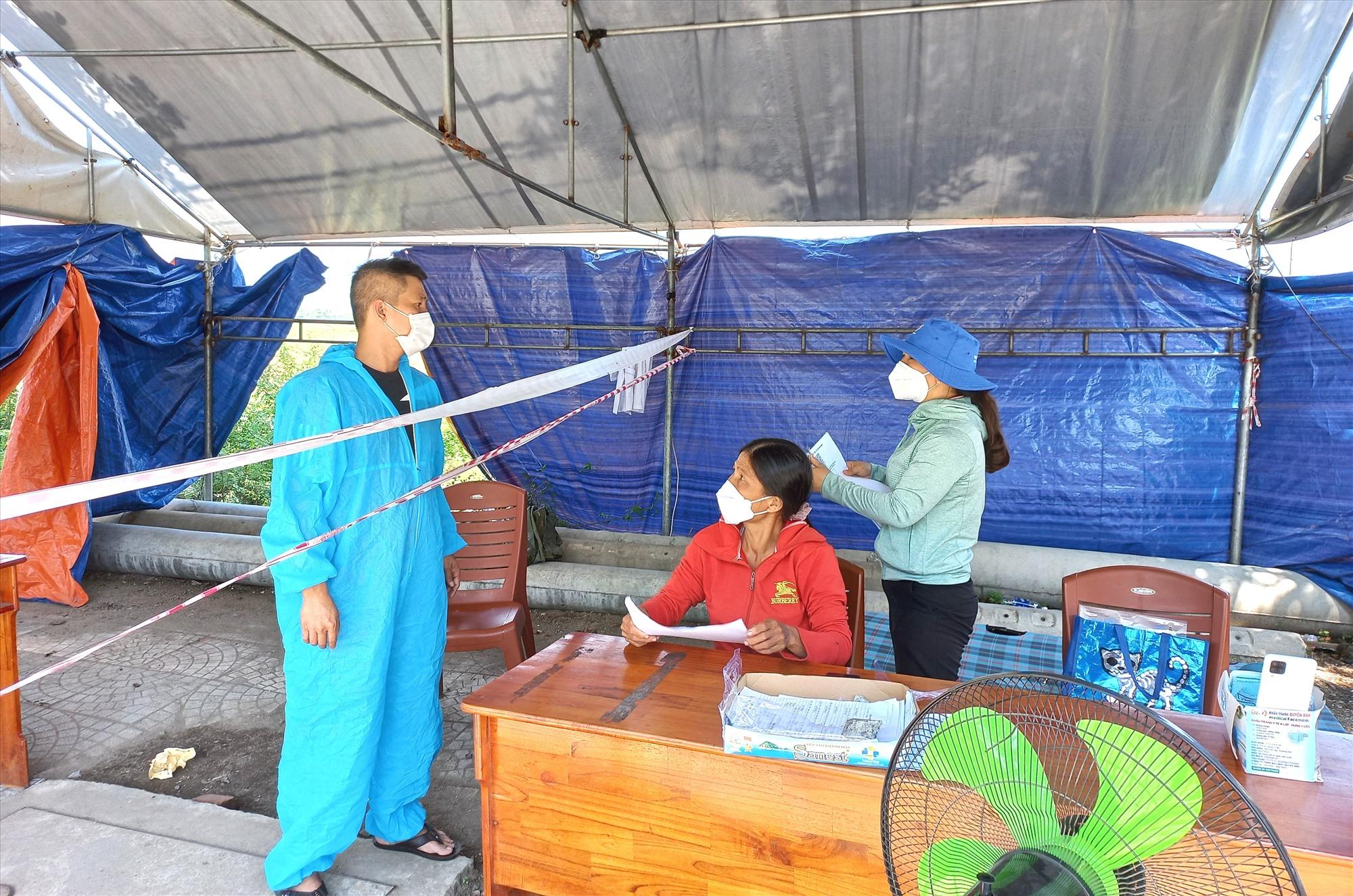 Nhân viên chốt kiểm soát trên đường Hùng Vương (thị trấn Ái Nghĩa) kiểm tra lái xe từ Đà Nẵng vào trưa 1.10. Ảnh: CT