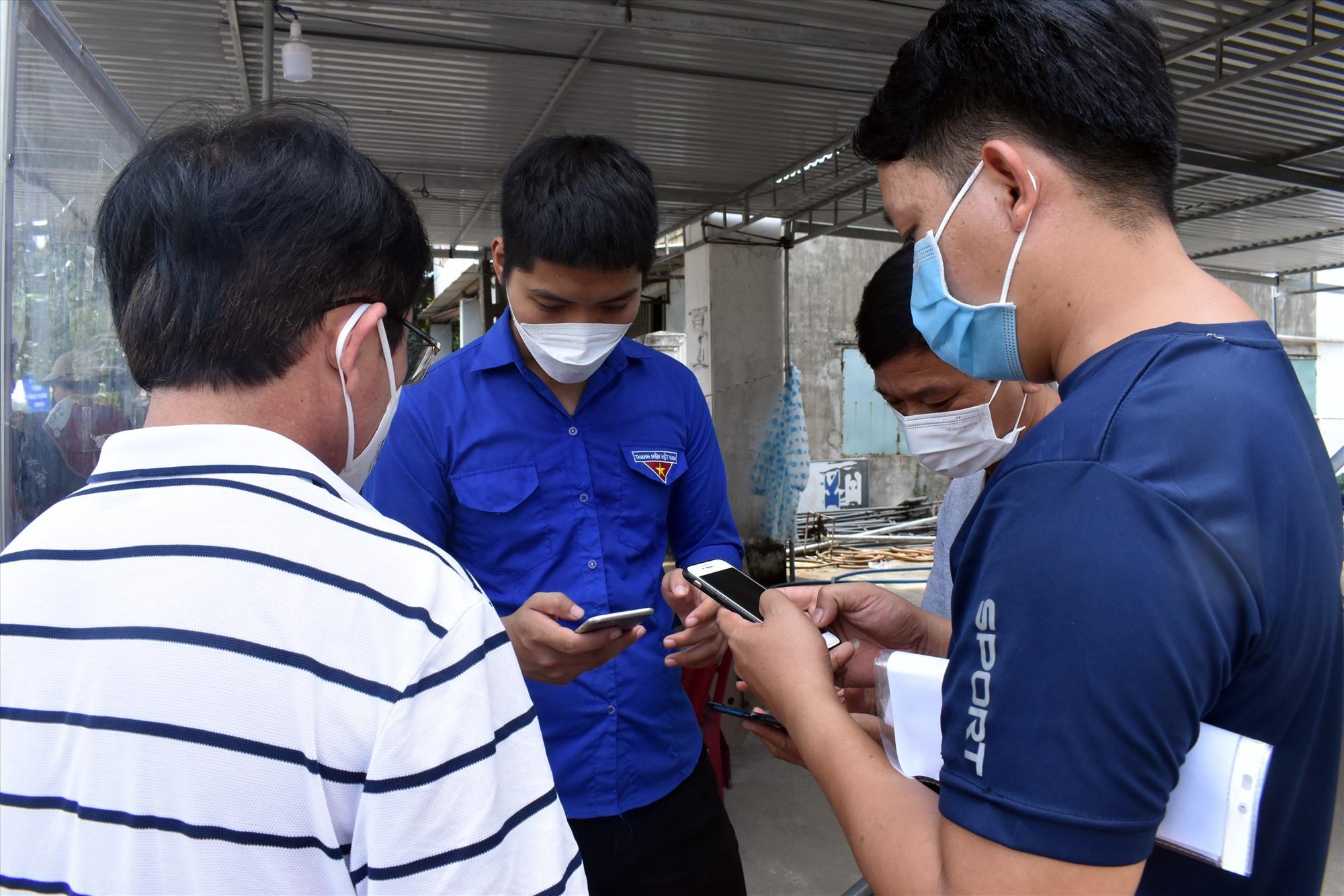 Lực lượng hỗ trợ hướng dẫn người dân kê khai y tế trến điện thoại thông minh - Ảnh: V.L