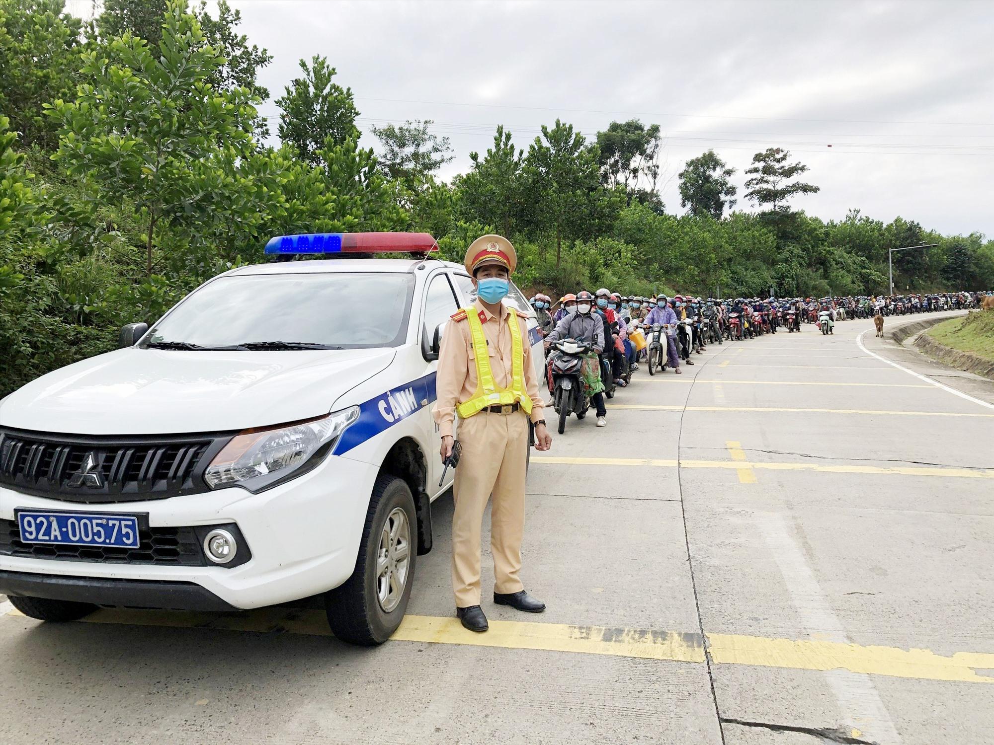 Cảnh sát giao thông dẫn đường cho đoàn người hồi hương về quê bằng xe máy.
