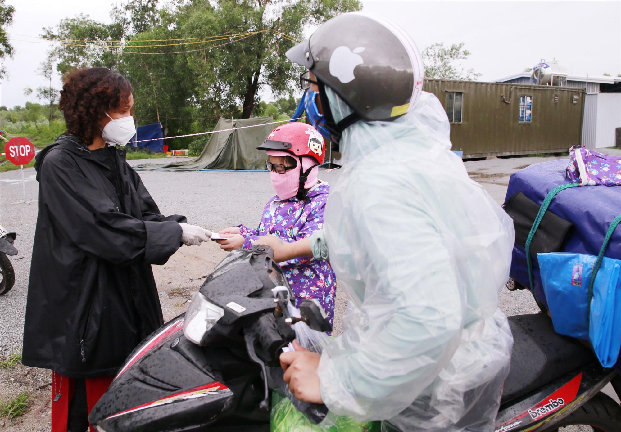 Chị Lương Thúy Hà (bên trái) tặng tiền hỗ trợ đồng bào về quê tại chốt kiểm soát Dốc Sỏi.