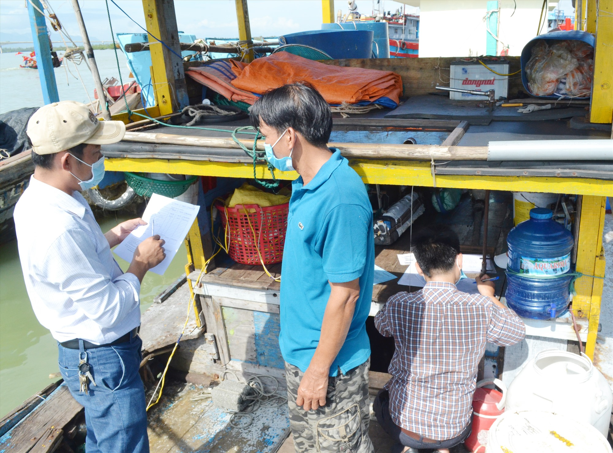 Các đăng kiểm viên thực hiện đăng kiểm trên tàu cá của ngư dân huyện Núi Thành. Ảnh: VIỆT NGUYỄN