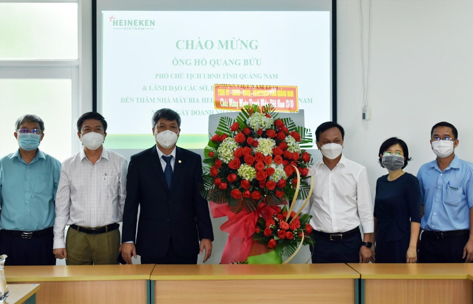 Phó Chủ tịch UBND tỉnh Hồ Quang Bửu tặng hoa chúc mừng Ngày Doanh nhân Việt Nam cho đại diện Nhà máy bía Heineken Việt Nam - Ảnh: V.L