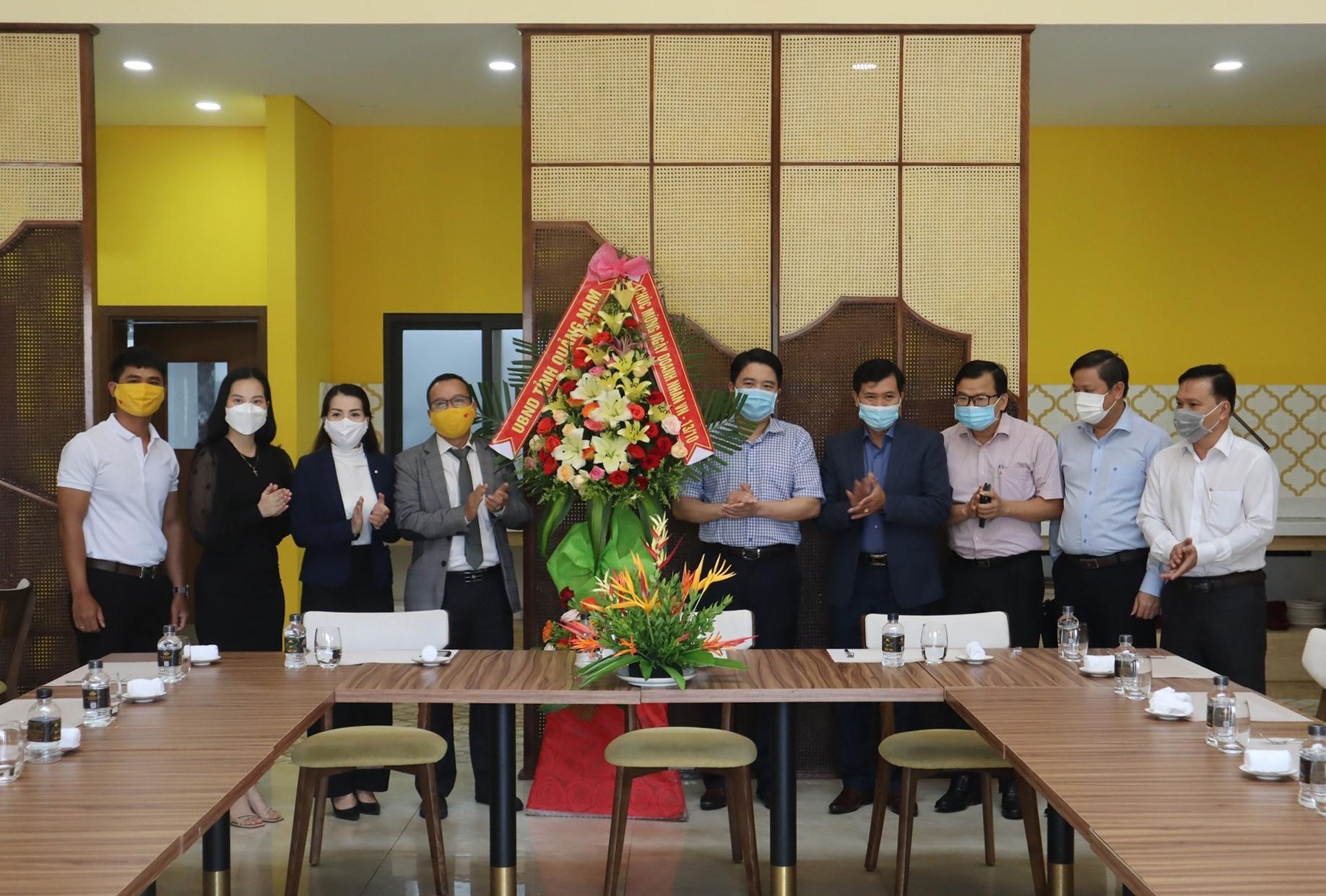 Lãnh đạo tỉnh tặng hoa mừng Ngày Doanh nhân Việt Nam cho đại diện quản lý Công viên Ký ức Hội An. Ảnh: Q.T