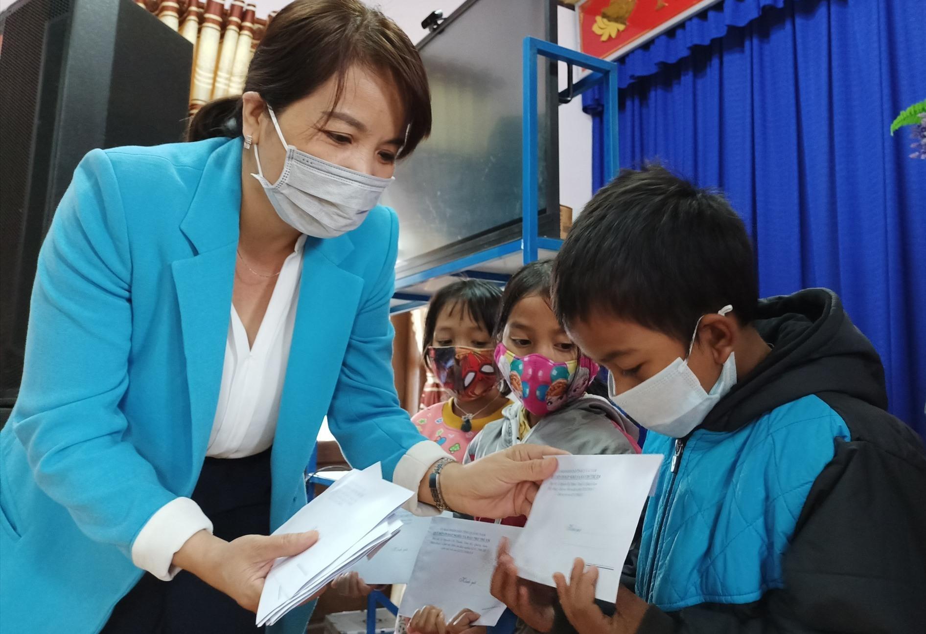 """Bà Lưu Thị Bích Ngọc, Phó Giám đốc Sở LĐ-TB và XH tỉnh trao """"học bổng"""" cho các em. Ảnh: ĐH"""