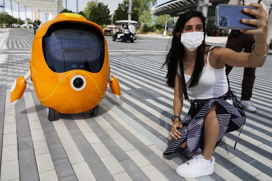 Một du khách chụp ảnh tự sướng với một chú rô bốt đang lang tháng tại Expo 2020 Dubai. Ảnh: AP