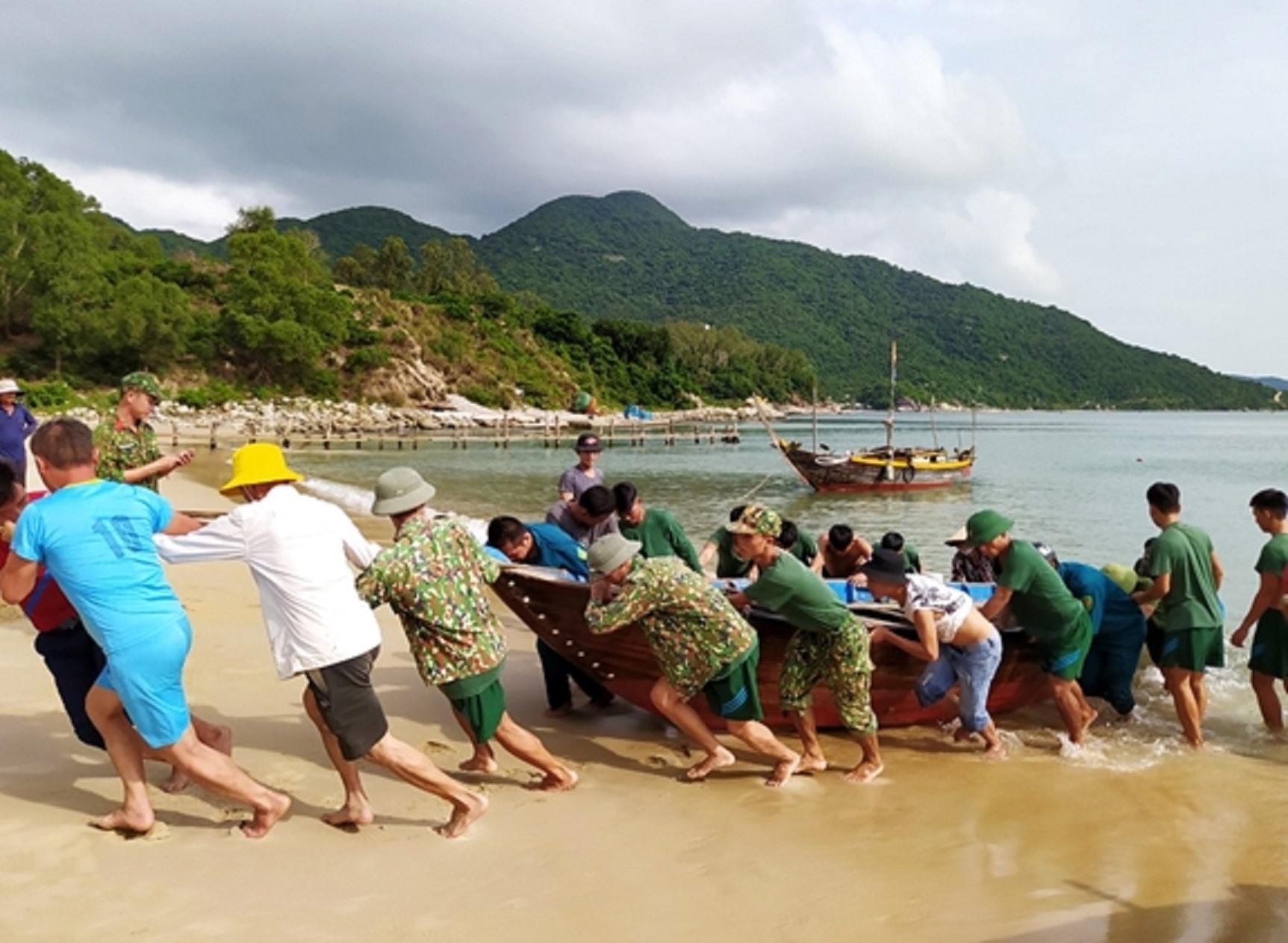 Cán bộ, chiến sĩ Tiểu đoàn hỗn hợp 70 giúp dân di chuyển thuyền đến vị trí an toàn. Ảnh: N.D