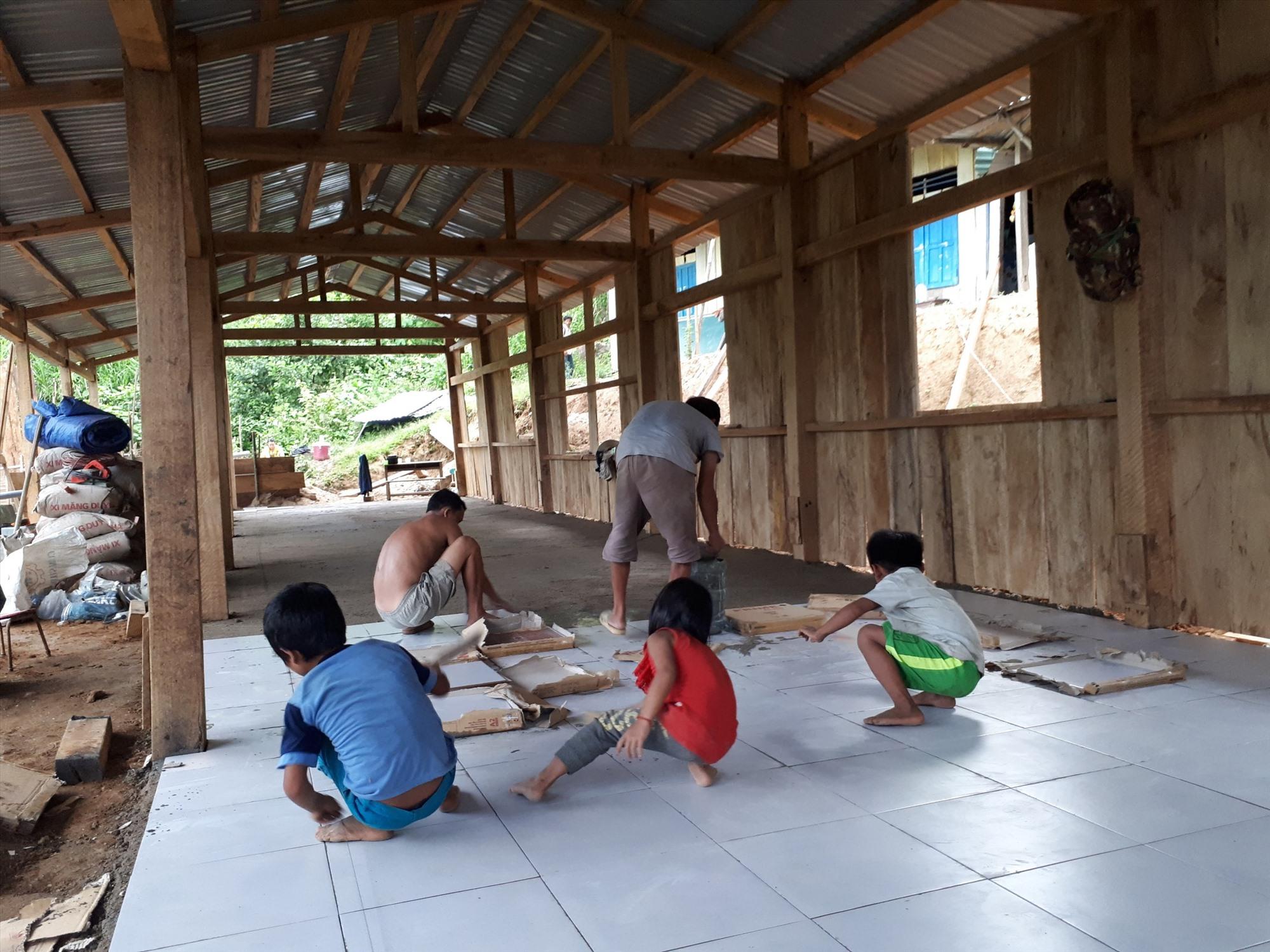 Bà con nhân dân và các em học sinh cùng tham gia một công đoạn nhỏ trong quá trình hoàn thiện ngôi trường. Ảnh: LÊ THANH VY