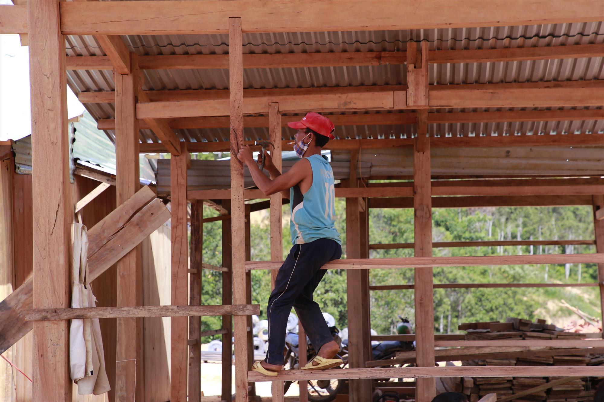 Người dân dựng nhà mới nơi khu tái định cư. Ảnh: T.C