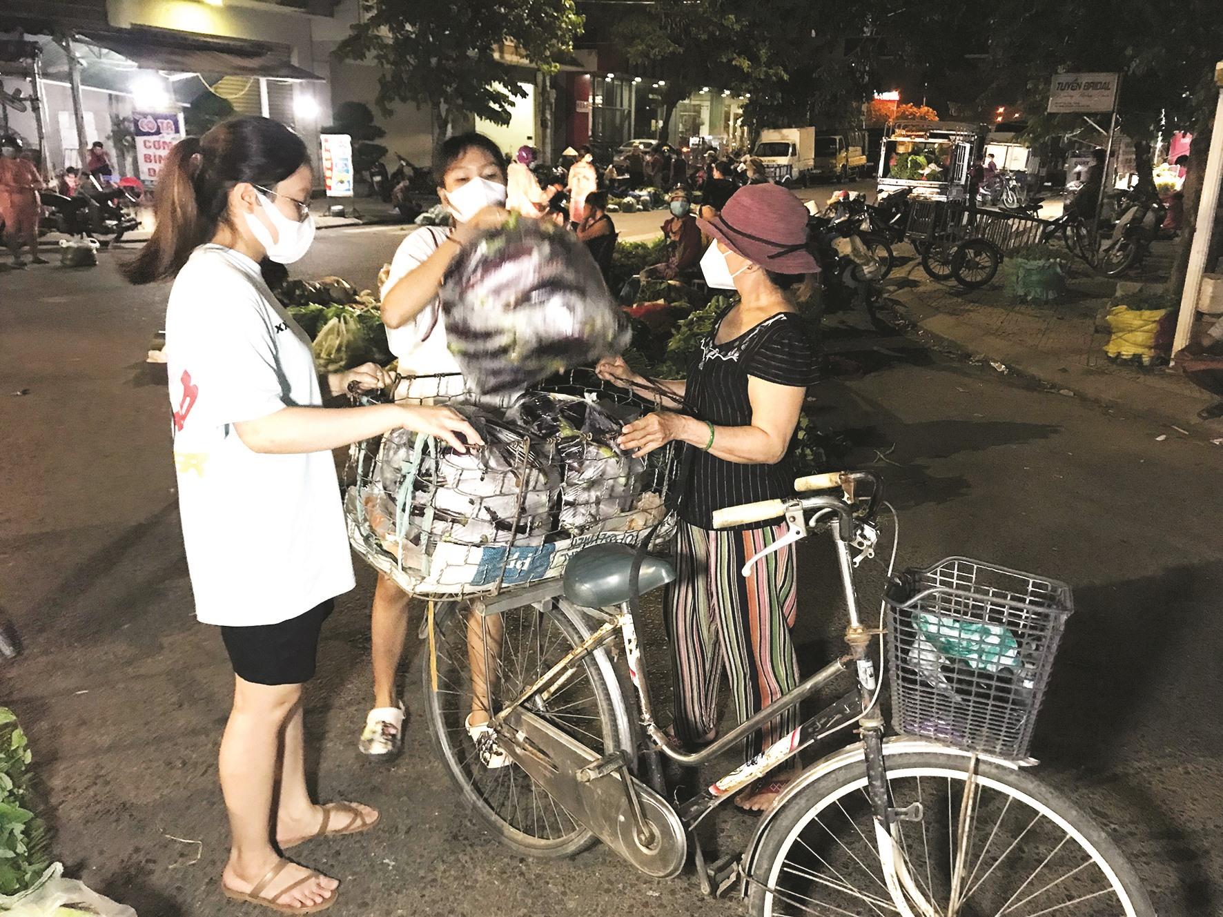 Hai sinh viên Đại học Ngoại ngữ Đà Nẵng phụ mẹ gom hàng.