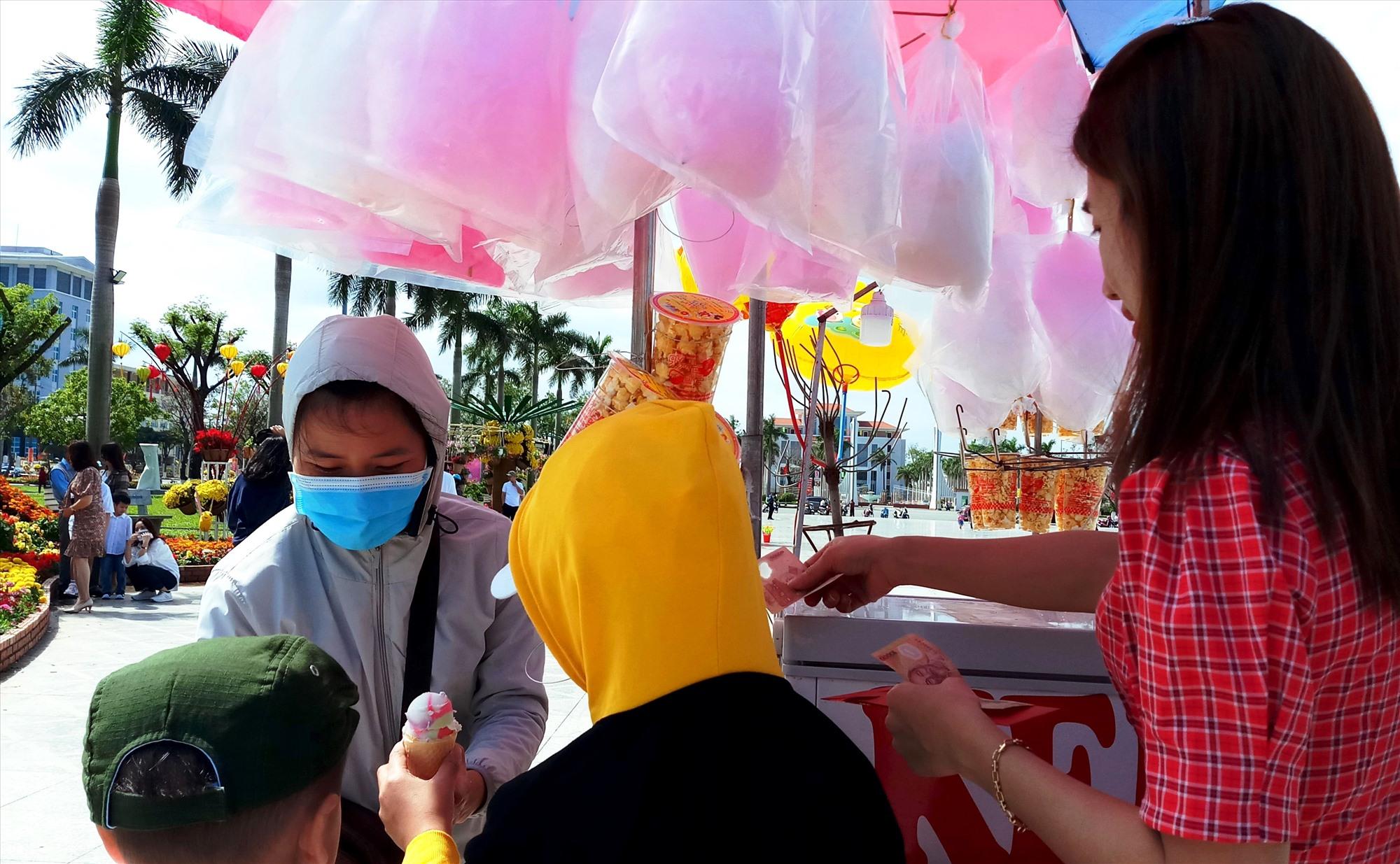"""Không chỉ người bán bong bóng dạo, những ngày tết, ở Quảng trường 24.3 """"hội tụ"""" rất nhiều người tìm đến để mưu sinh. Trong ảnh, một người phụ nữ dùng xe đẩy bán kem cho du khách. Ảnh: Đ.N"""