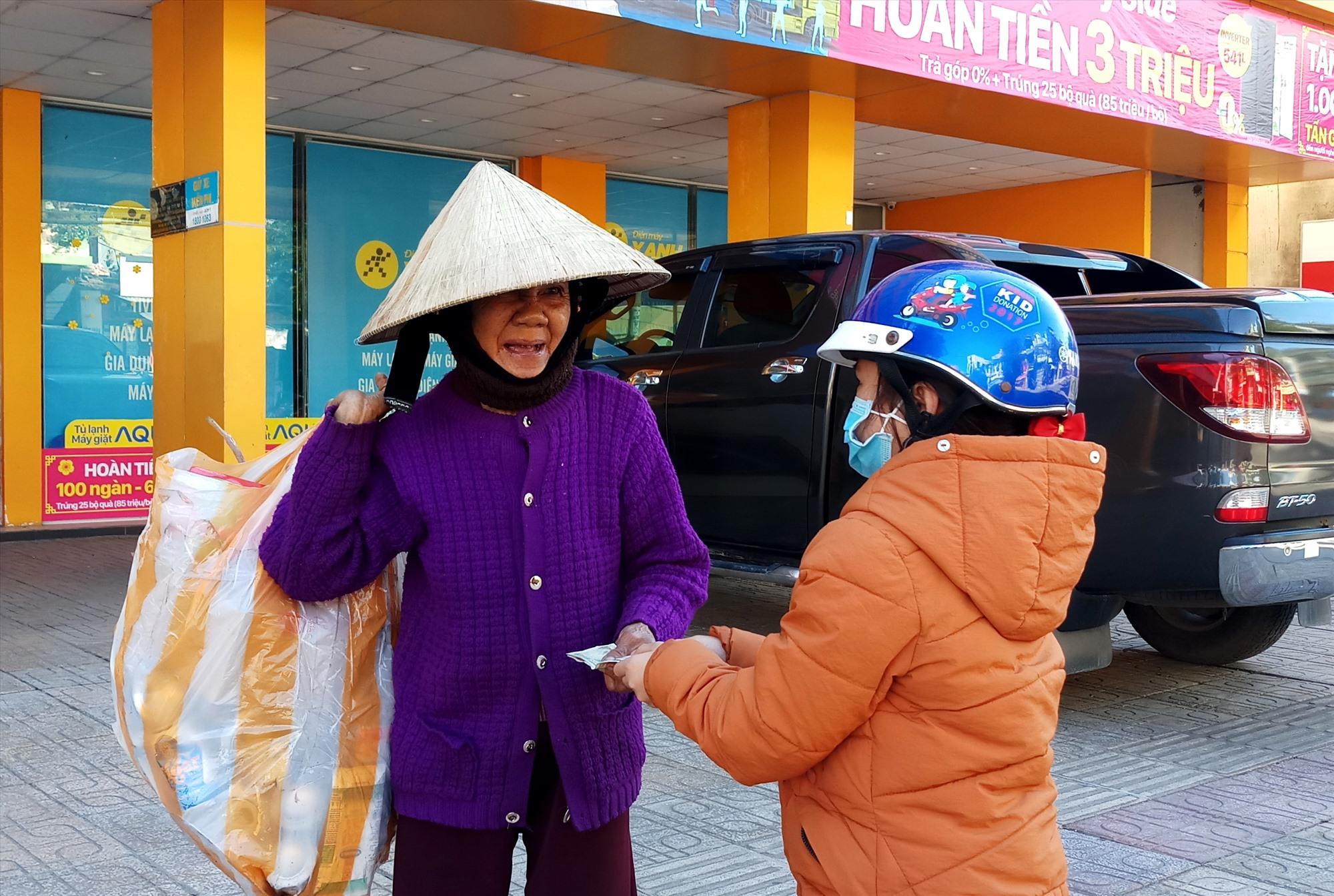 Niềm vui của một cụ bà ve chai khi nhận được lì xì từ một bé gái đi đường. Ảnh: Đ.N