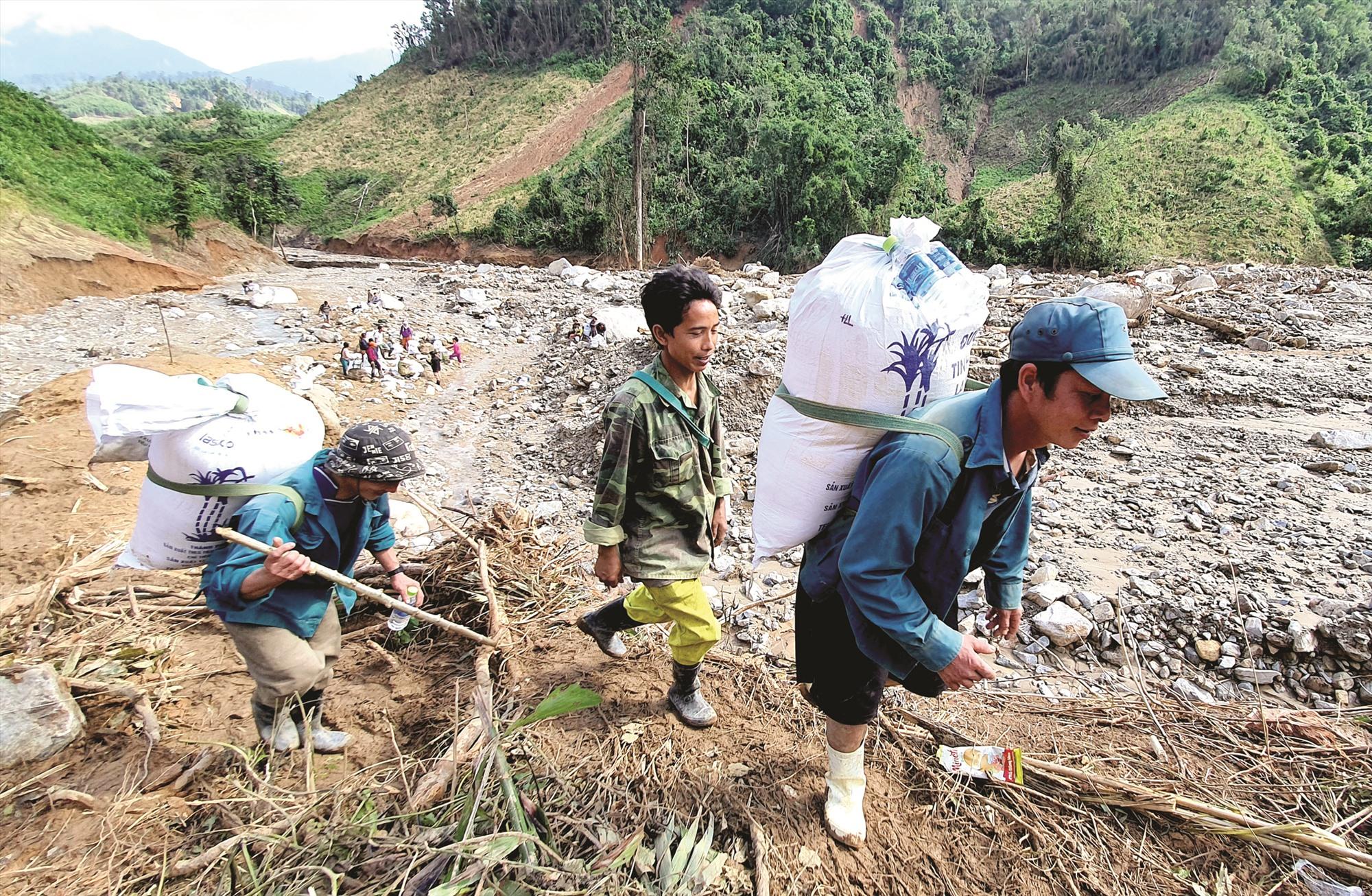 Gùi cõng lương thực, thực phẩm tiếp tế bà con vùng cô lập do sạt lở, lũ quét sau bão số 9 ở Phước Sơn. Ảnh: HUỲNH CHÍN