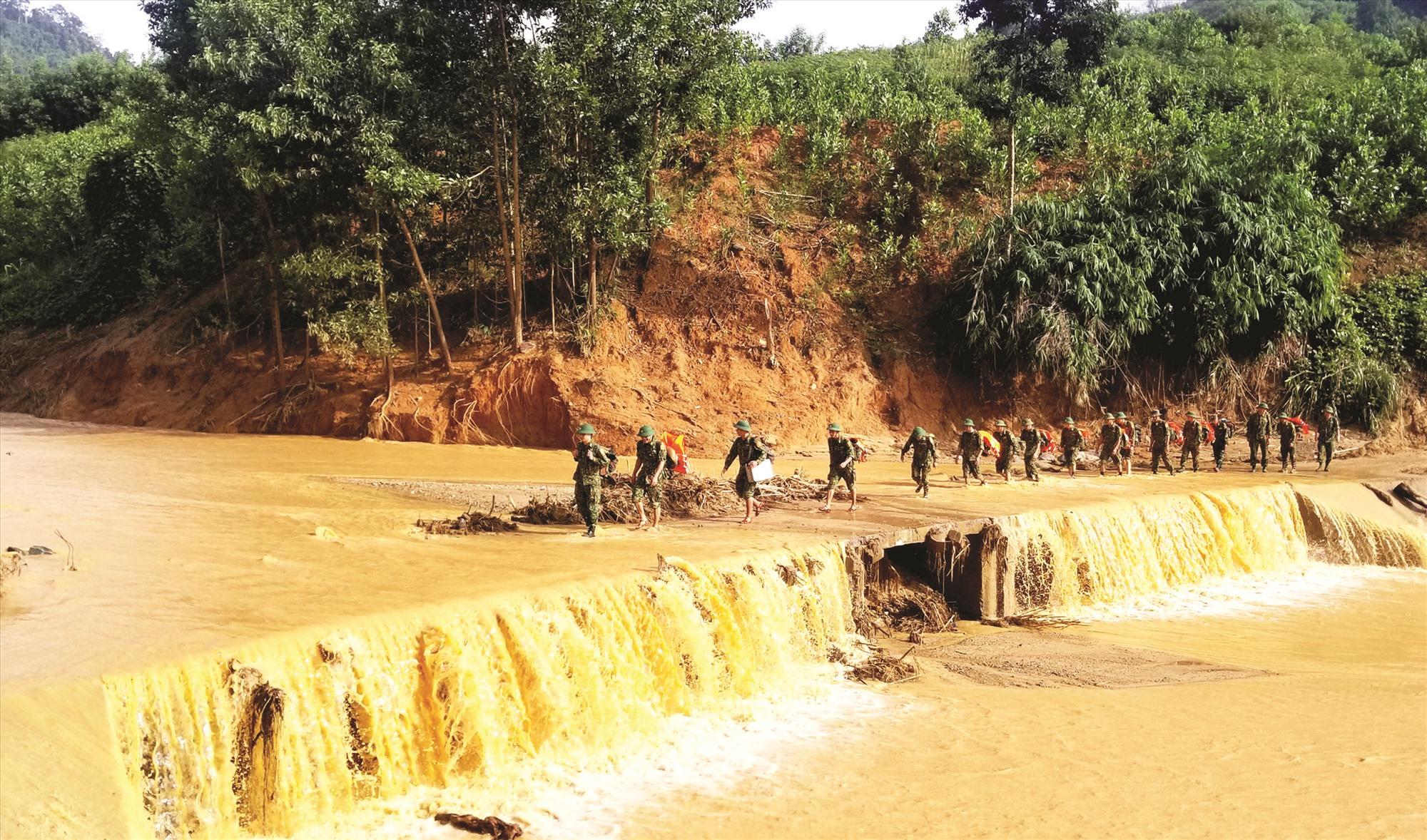 Bộ đội hành quân qua con suối dẫn vào xã Phước Công. Từ nơi này, phải mất hàng chục cây số đường rừng nữa mới tiếp cận được vùng sạt lở núi ở xã Phước Lộc (Phước Sơn). Ảnh: G.C