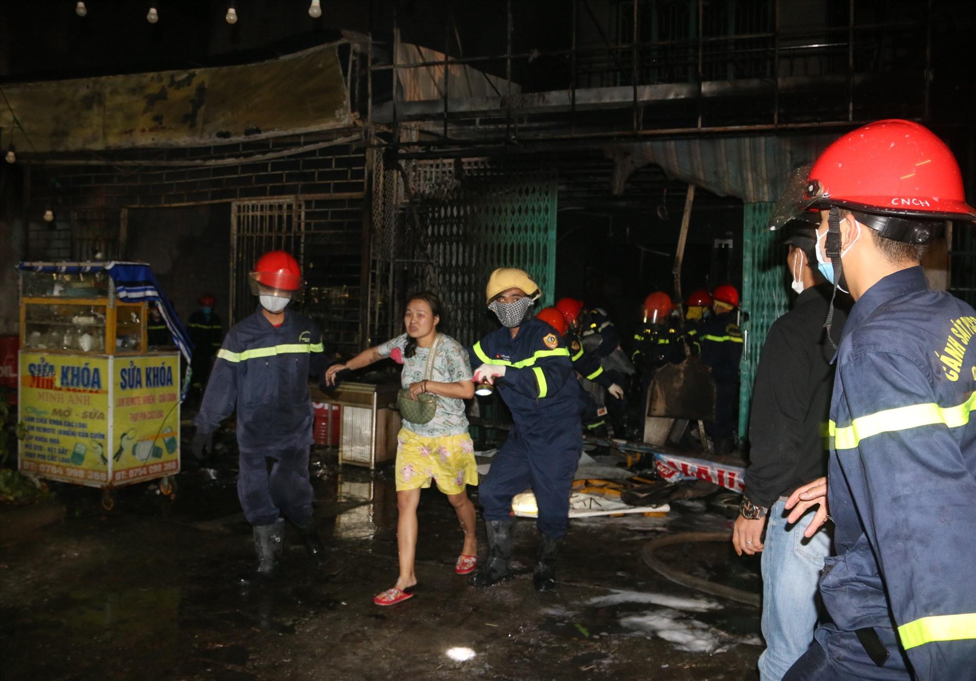 Lực lượng cứu hộ đưa nạn nhân mắc kẹt trong đám cháy ra ngoài. Ảnh: Công an cung cấp