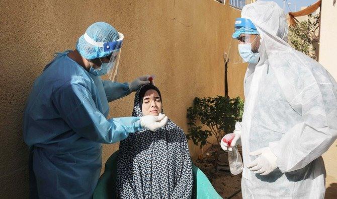 Nhân viên y tế Palestine lấy mẫu xét nghiệm corona cho một người dân ở phía nam Dải Gaza. Ảnh: AFP