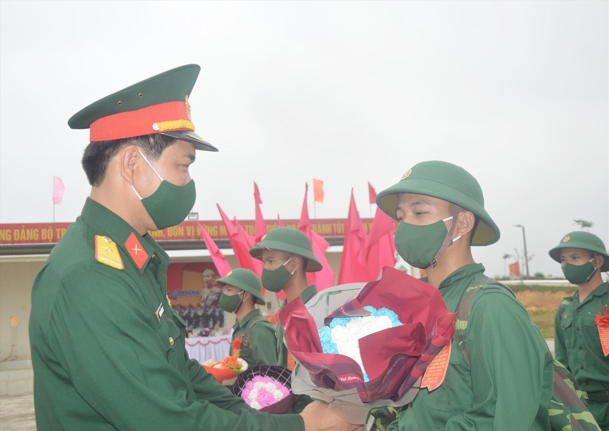 Lãnh đạo Trung đoàn 885 tặng hoa chúc mừng tân binh. Ảnh: T.A
