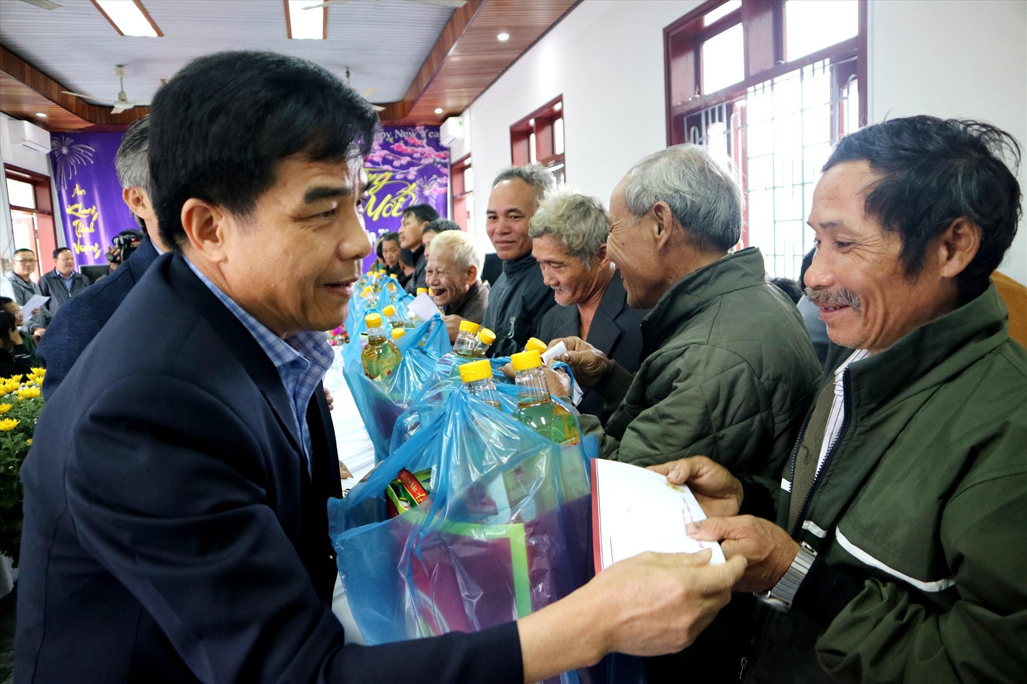 Phó Bí thư Thường trực Tỉnh ủy Lê Văn Dũng trao qâuf tết cho các già làng, người có uy tín ở Bắc Trà My. Ảnh: A.N