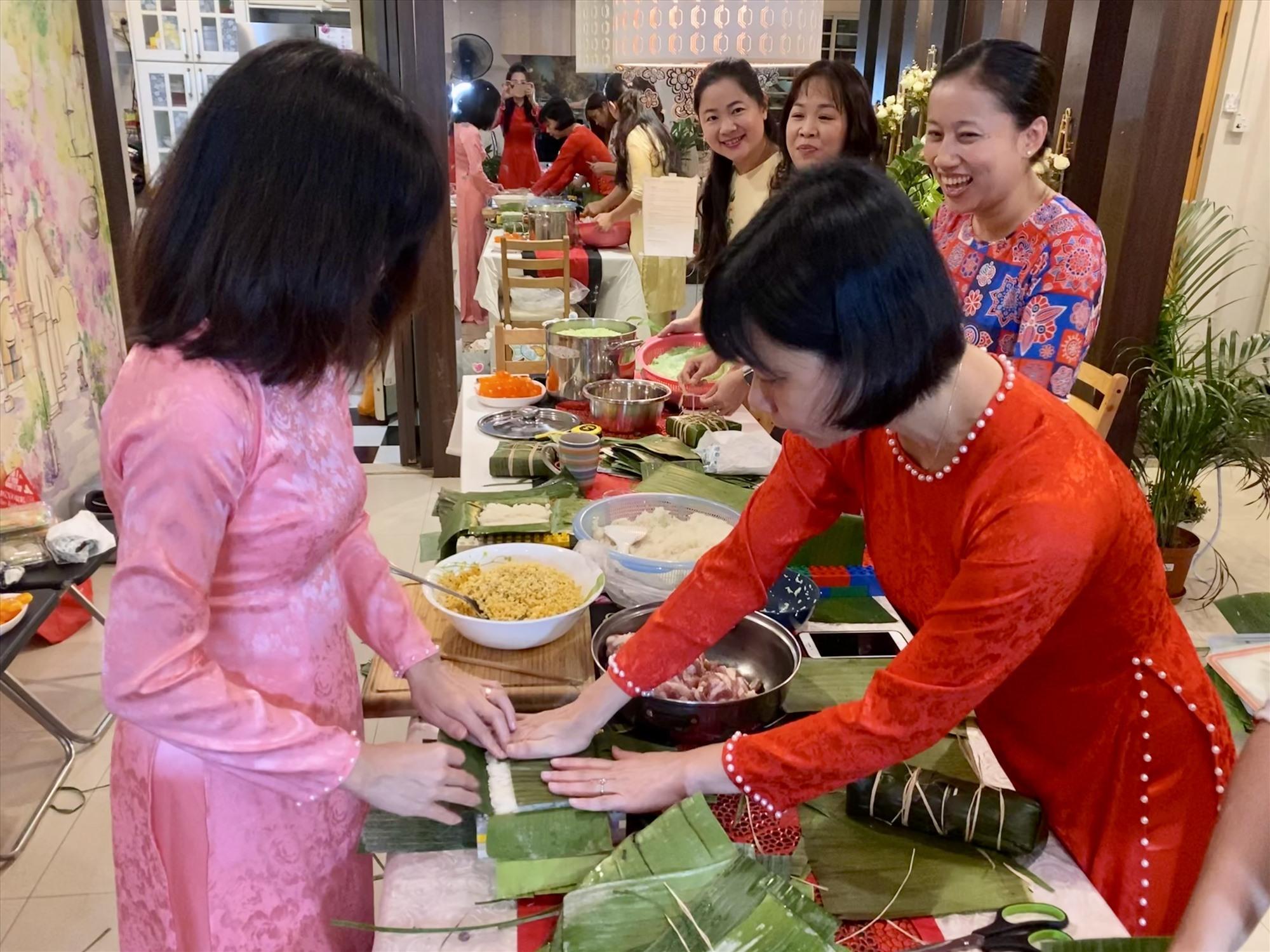 Tác giả (phải) hướng dẫn một bạn trẻ người Việt lần đầu gói bánh đón Tết xa quê.