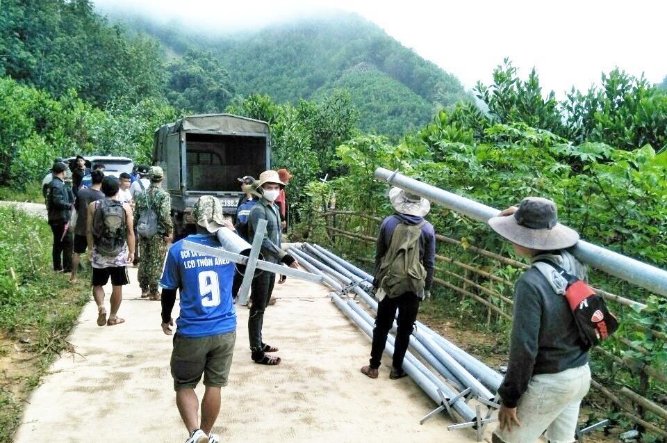 Dân quân, thanh niên vận chuyển hàng trăm kg thiết bị chiếu sáng lội bộ vào làng Aur. Ảnh: ĐÌNH HIỆP