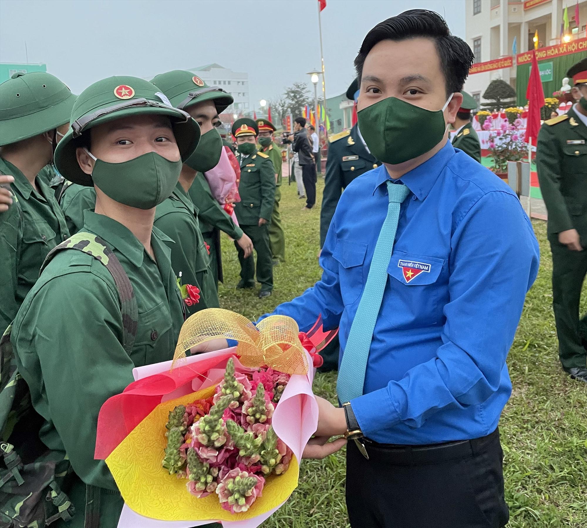 Cán bộ đoàn tặng hoa, động viên thanh niên lên đường thi hành nghĩa vụ quân sự. Ảnh: T.S