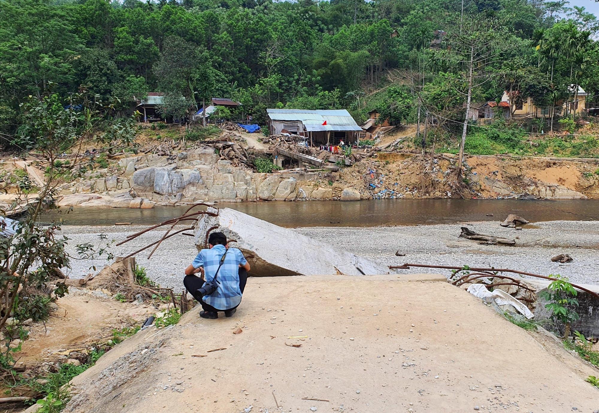 Cầu treo bị cuốn trôi gây chia cắt đôi bờ sông Bui. Ảnh: B.A