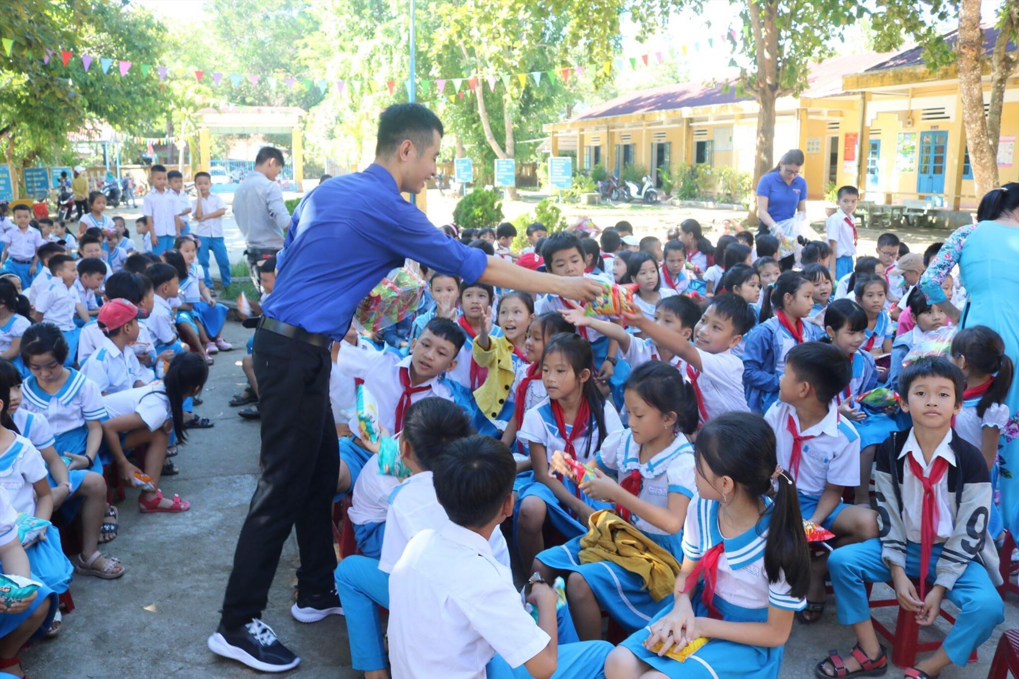 Anh Bảo tham gia ngoại khoá tiếng anh và phát kẹo, bánh cho học sinh tiểu học trên địa bản tỉnh Quảng Nam. Ảnh: QUỐC BẢO