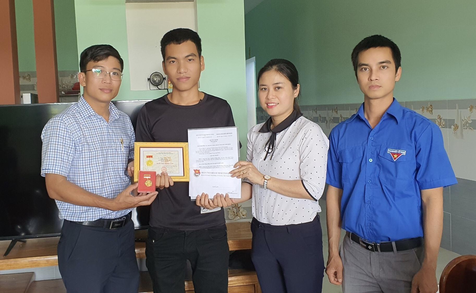 Anh Nguyễn Xuân Đức cùng cán bộ đoàn địa phương trao tặng Huy hiệu Tuổi trẻ dũng cảm cho anh Trần Văn Trong. Ảnh: T.ĐẠT