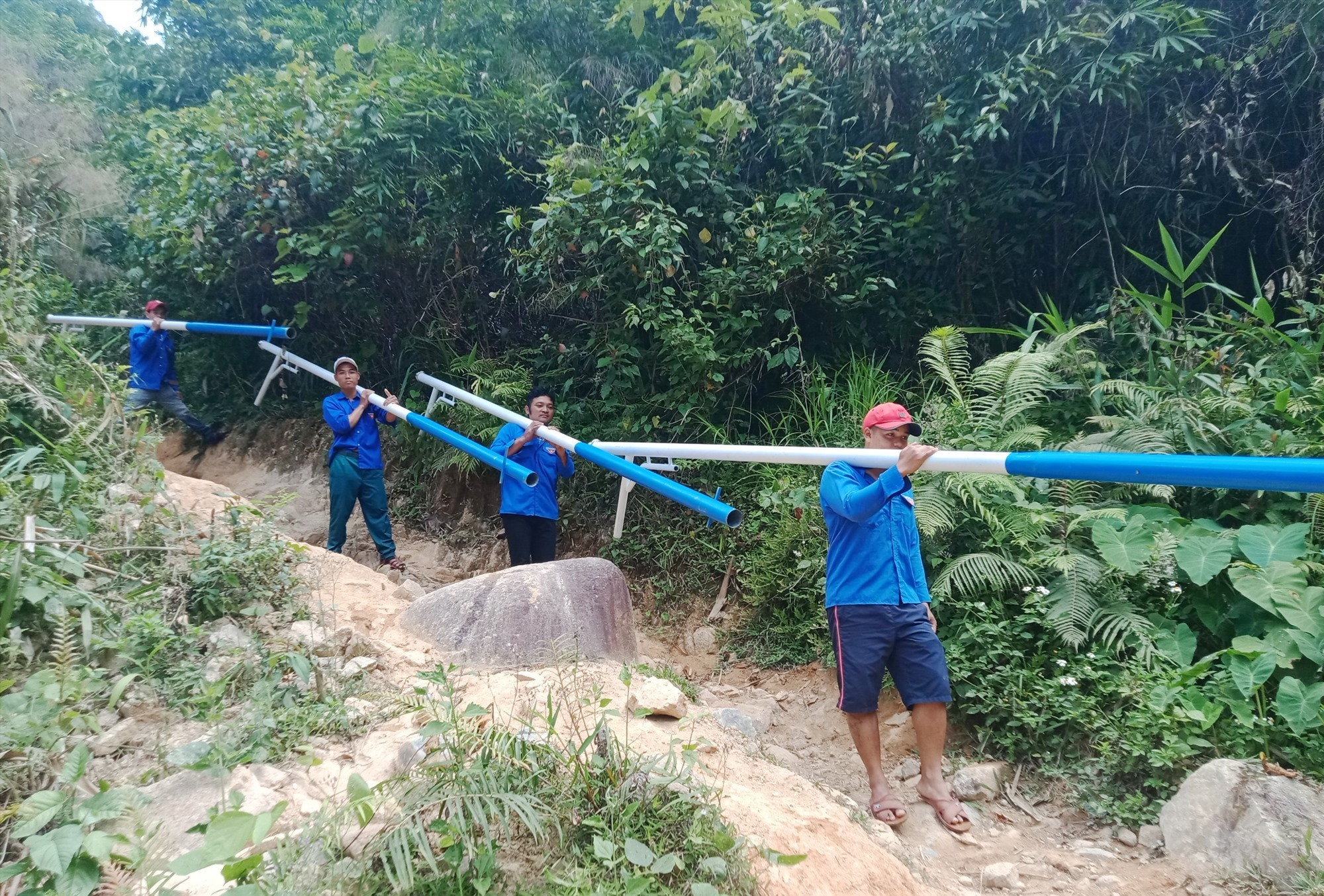 Thanh niên tình nguyện cuốc bộ vận chuyển vật liệu vào Peetapooc. Ảnh: THẾ ANH