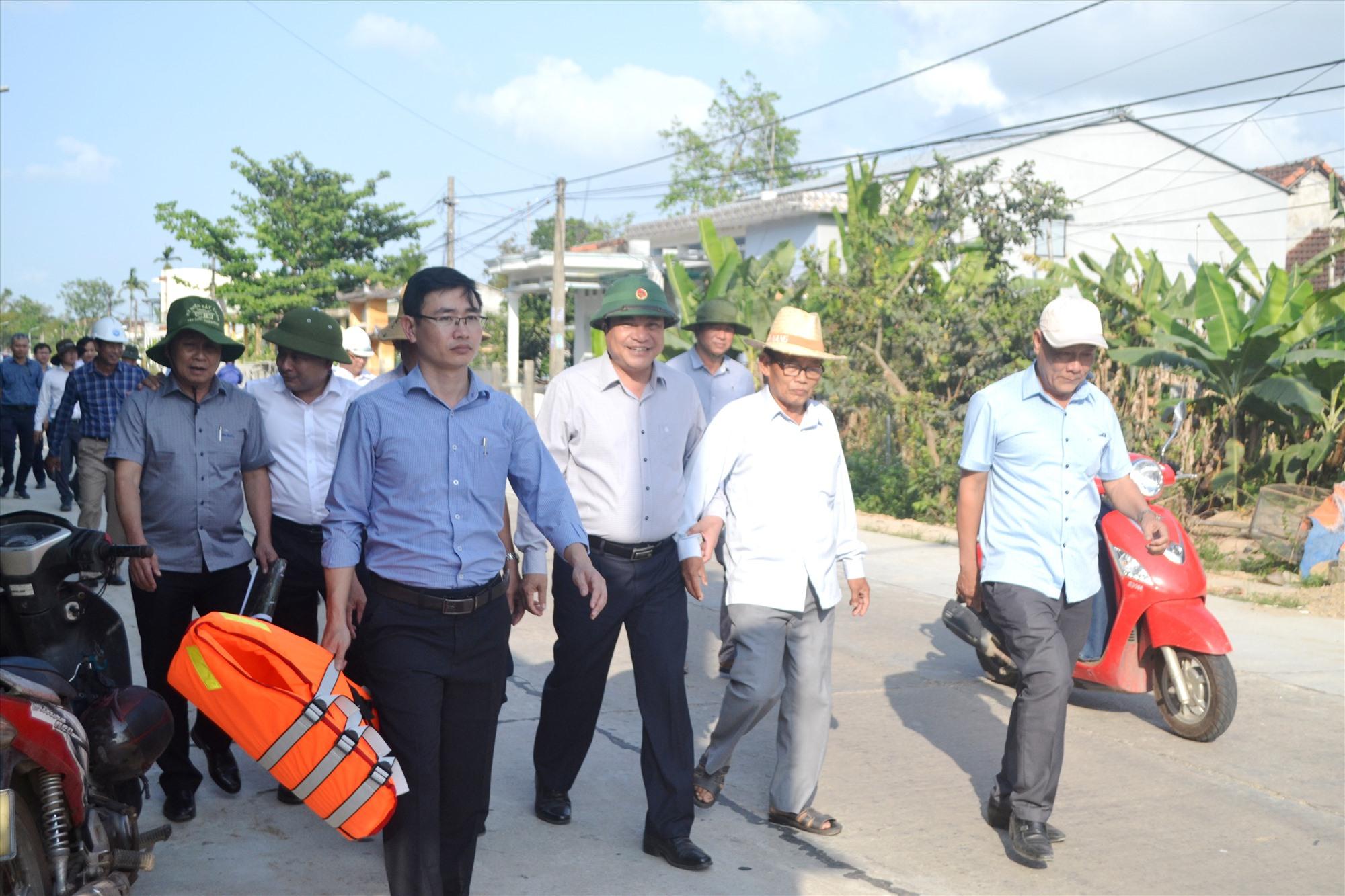 Bí thư Tỉnh ủy Phan Việt Cường đi cùng với một cán bộ lão thành cách mạng sinh sống tại xã Duy Tân (Duy Xuyên). Ảnh: CT