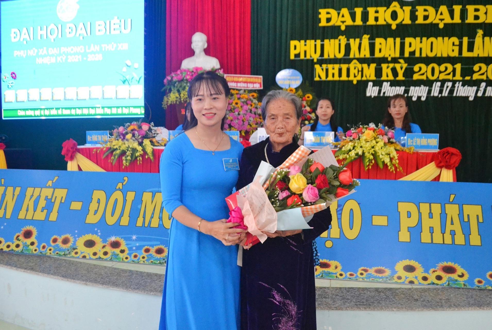 Chủ tịch Hội LHPN xã Đại Phong - bà Tào Thị Bích Thủy trao tặng quà và hoa cho Bà mẹ Việt Nam anh hùng. Ảnh: KK