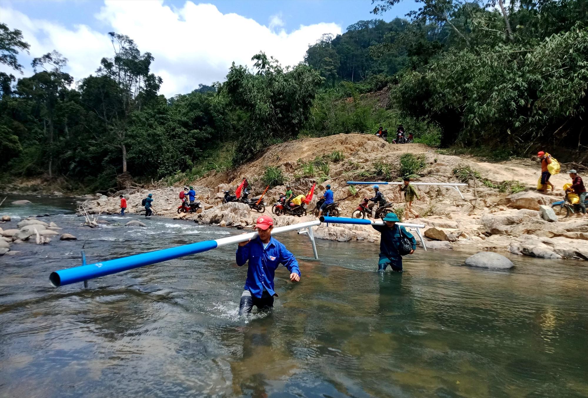 Thanh niên huyện Nam Giang vận chuyển vật liệu điện năng lượng mặt trời đến cụm dân cư Pêtapot. Ảnh: Đ.N