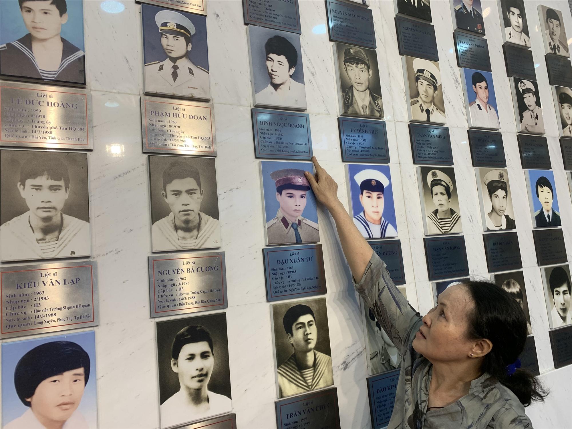 Bà Đỗ Thị Hà bên di ảnh chồng tại Khu tưởng niệm chiến sĩ Gạc Ma. Ảnh: T.M