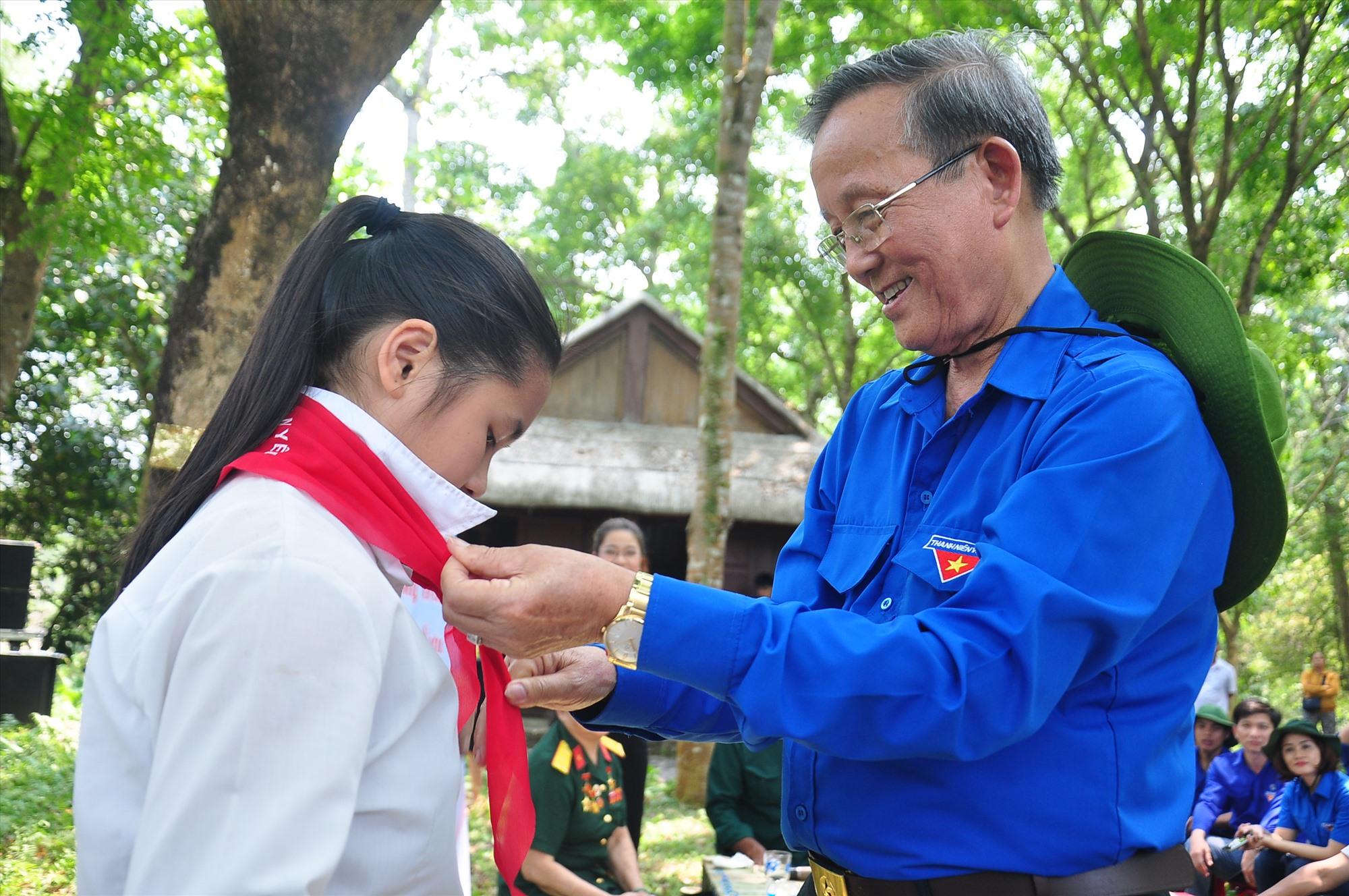 Ông Đỗ Tấn Hùng tặng một học sinh huyện Bắc Trà My chiếc khăn quàng đỏ - kỷ vật thời còn làm công tác đoàn. Ảnh: VINH ANH