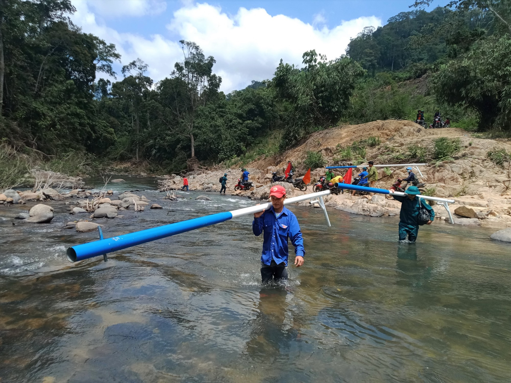Thanh niên Nam Giang vượt sông vận chuyển vật liệu lắp đặt điện chiếu sáng cho người dân cụm dân cư Pêtapooc, xã Đắc Pring.