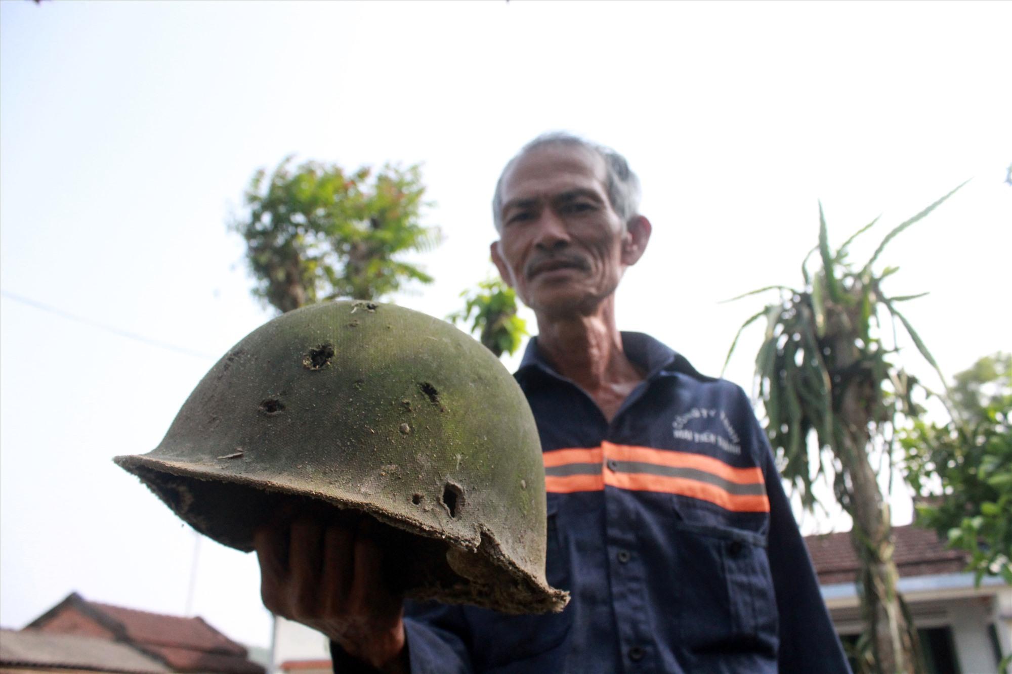 Ông Nguyễn Ngọc Thọ còn cất giữ chiếc mũ cối của địch lỗ chỗ vết đạn. Ảnh: T.C