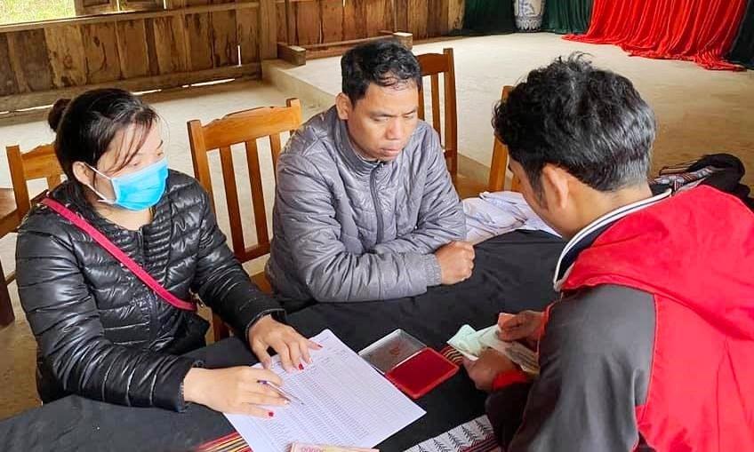 Cán bộ Ủy ban MTTQ Việt Nam huyện Tây Giang đang chi trả, tạm ứng cho hộ dân sữa chữa, làm mới nhà ở