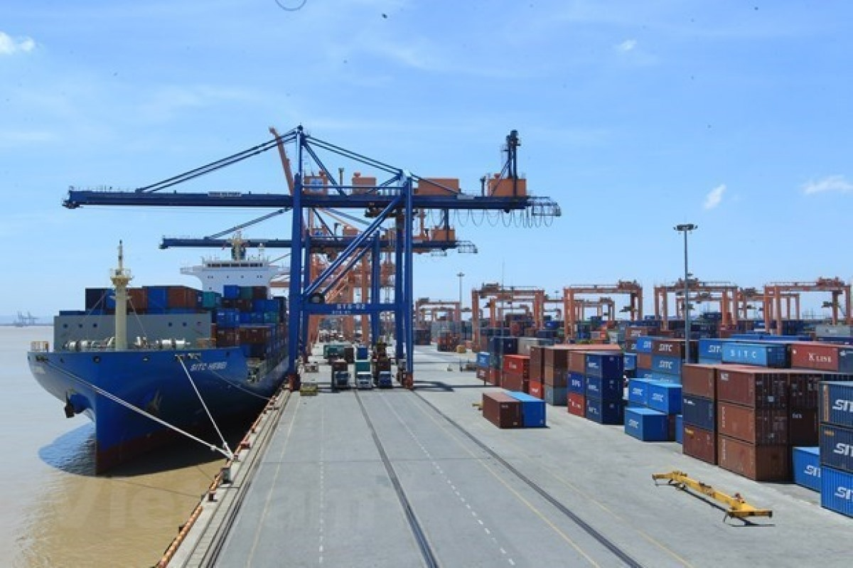 Unloading containers at a seapport in Vietnam (Photo: VNA)