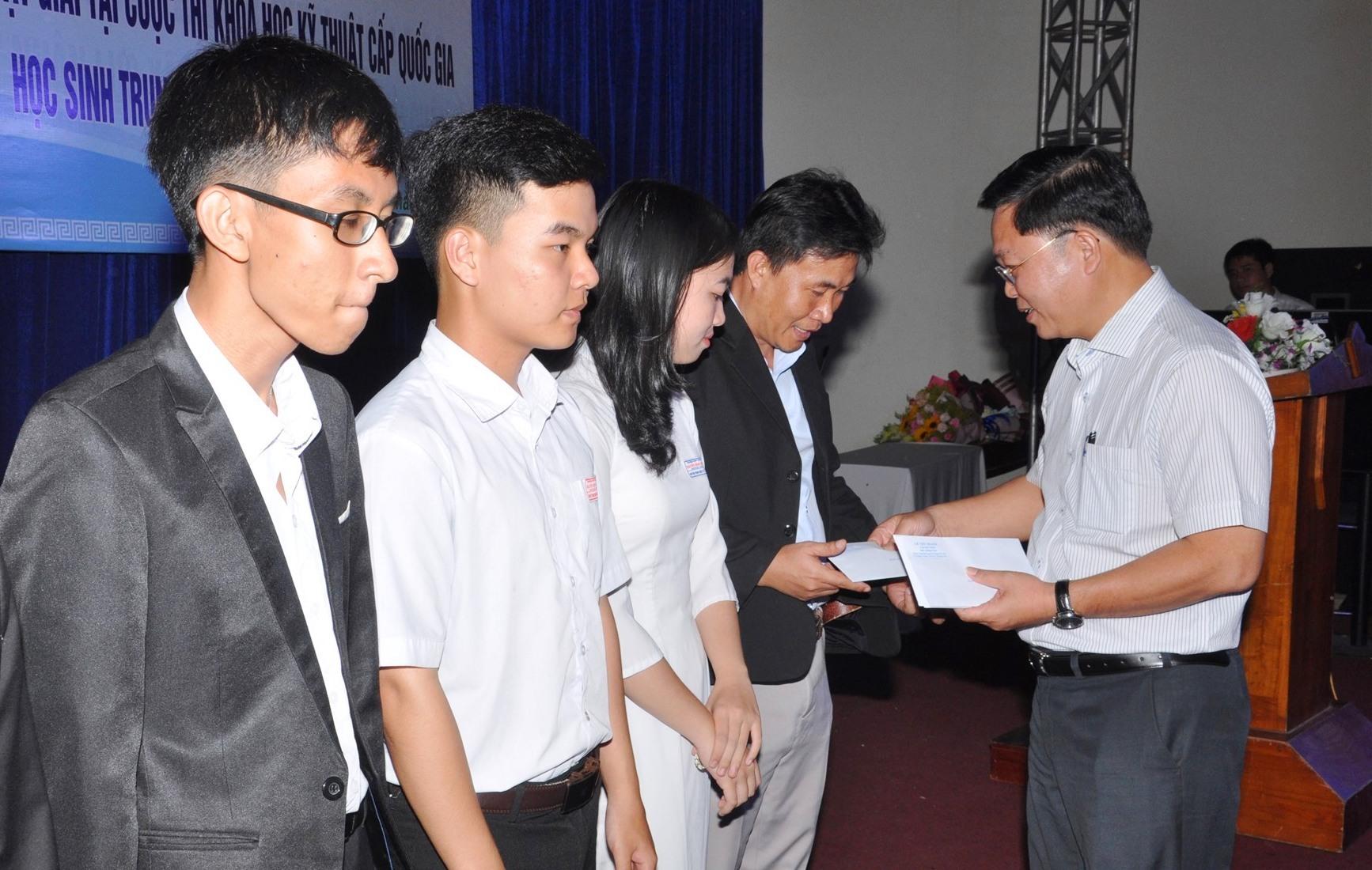 Chủ tịch UBND tỉnh Lê Trí Thanh tặng quà cá nhân cho giáo viên và học sinh. Ảnh: X.P