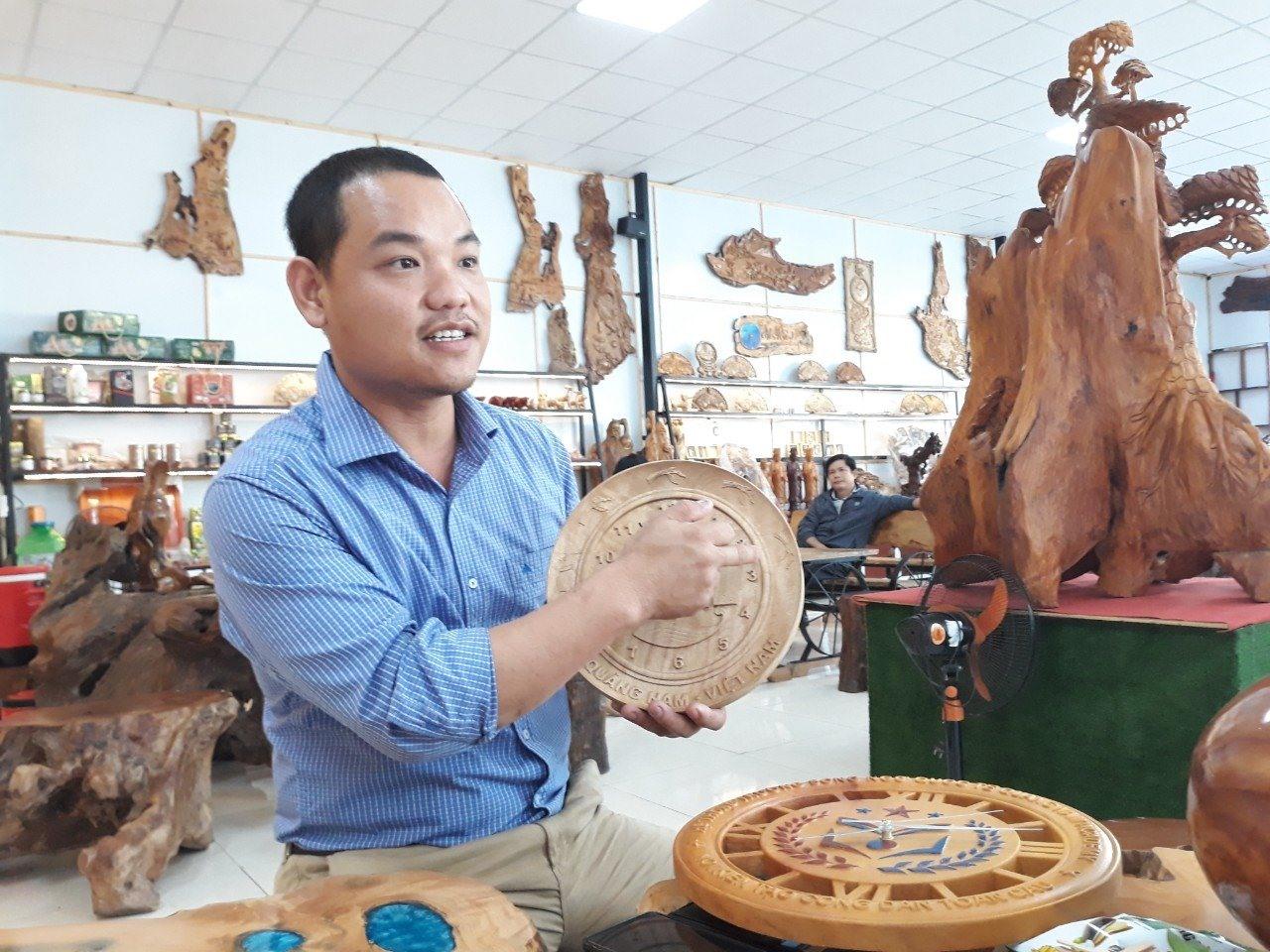 Ông Lê Hồng Thái giới thiệu sản phẩm mỹ nghệ bằng gỗ quế. Ảnh: C.N