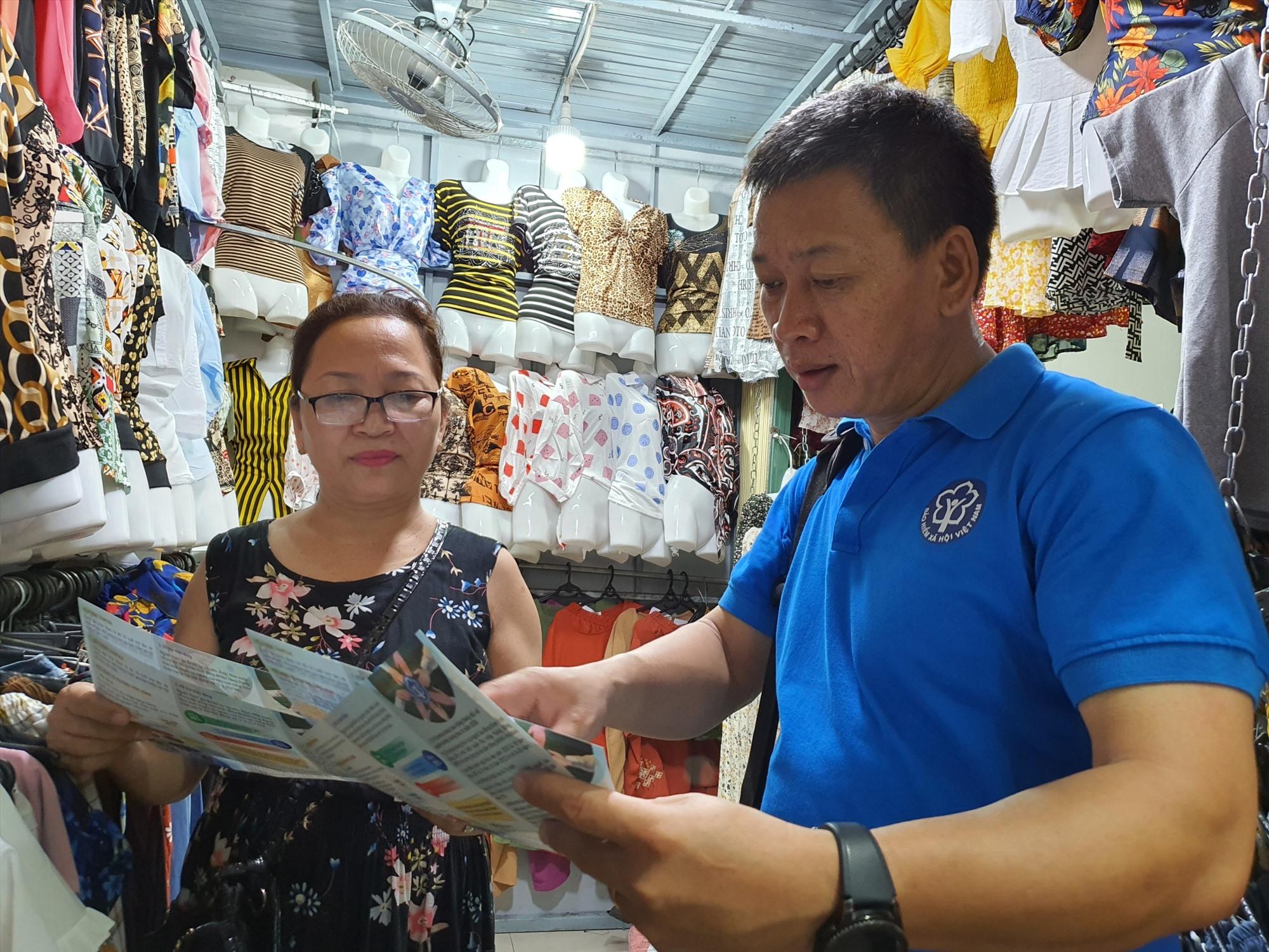 Cán bộ BHXH tỉnh tuyên truyền chính sách BHXH tự nguyện cho các tiểu thương chợ Tam Kỳ. Ảnh: H.Q