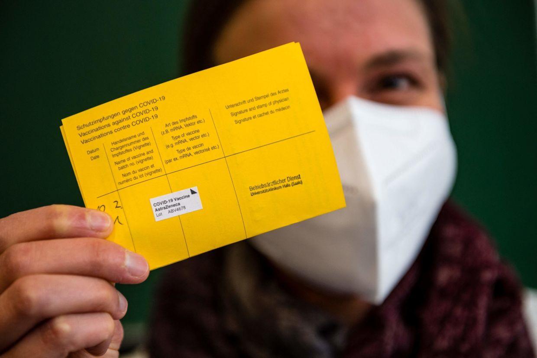 Một nhân viên y tế xuất trình thẻ tiêm chủng Covid-19 bổ sung của cô sau khi tiêm vắc-xin AstraZeneca Covid-19 ở Đức. FBI khuyến cáo mọi người không đăng ảnh thẻ tiêm chủng của họ lên mạng xã hội, đồng thời cảnh báo rằng thông tin này có thể bị những kẻ lừa đảo sử dụng để làm giả tài liệu. - AFP I